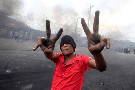 A supporter of Salvador Nasralla, presidential candidate for the Opposition Alliance Against the Dictatorship, gestures while standing at a barricade settled to block road during a protest caused by the delayed vote count for the presidential election in Tegucigalpa, Honduras December 1, 2017. REUTERS/Jorge Cabrera