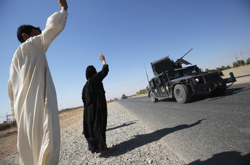 Iraqis wave to government forces as they arrive in the southern outskirts of Kirkuk on October 16, 2017 (AFP Photo/AHMAD AL-RUBAYE)
