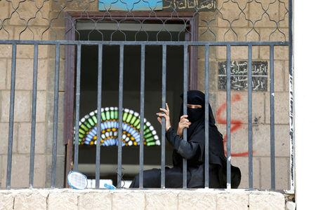 A woman displaced by the fighting in the Red Sea port city of Hodeidah sits behind a fence at a school allocated for IDPs in Sanaa, Yemen. REUTERS/Khaled Abdullah