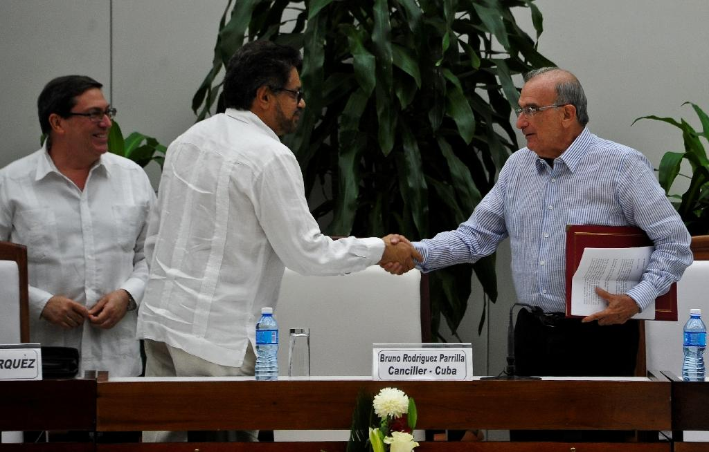 FARC-EP leftist guerrilla commander Ivan Marquez (C) and the head of the Colombian delegation for peace talks Humberto de la Calle (R) shake hands after signing a new peace agreement on November 12, 2016 (AFP Photo/Yamil Lage)