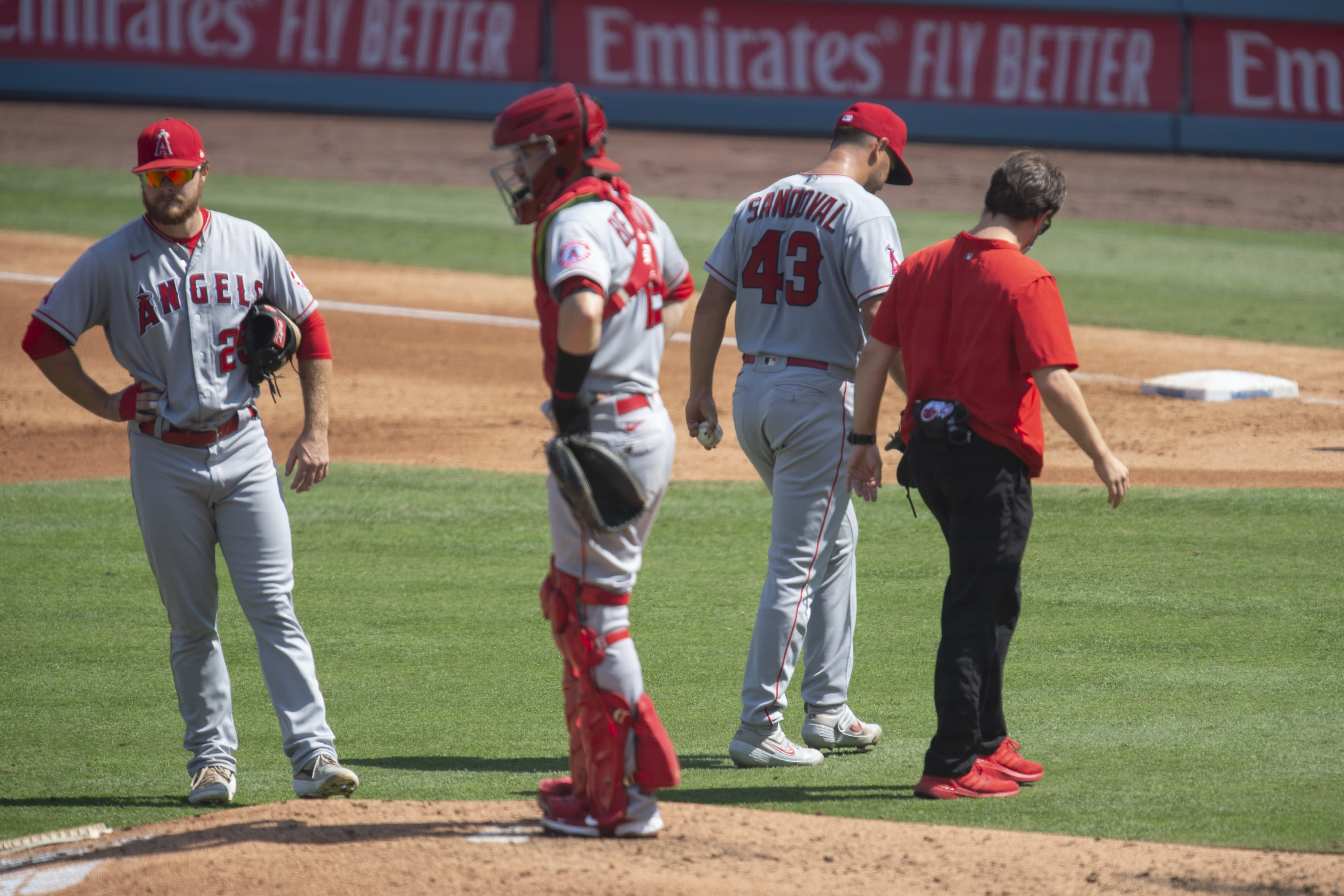 Los Angeles Angels starting pitcher Patrick Sandoval, second from right, exits with an injury during the third inning of a baseball game against the Los Angeles Dodgers in Los Angeles, Sunday, Sept. 27, 2020. (AP Photo/Kyusung Gong)