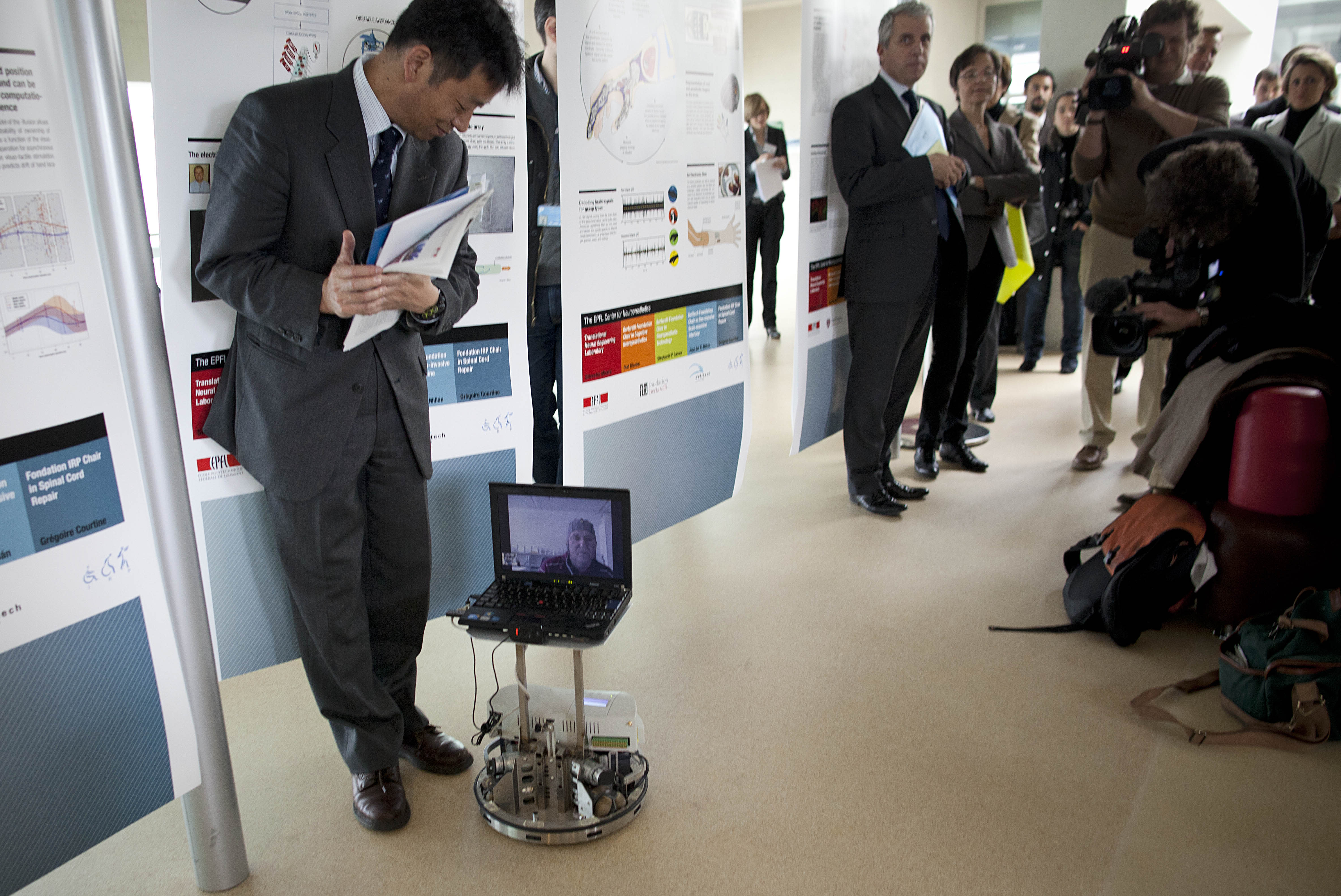 A spectator moves out of the way as Mark-Andre Duc, seen on the computer screen, directs a robot at Switzerland's Federal Institute of Technology in Lausanne, Switzerland, Tuesday, April 24, 2012. From the hospital 100 kilometers (62 miles) away, Duc imagined lifting his fingers to direct a robot. Swiss scientists demonstrated with this test how a partially paralyzed person can control a robot using brain signals alone. (AP Photo/Anja Niedringhaus)