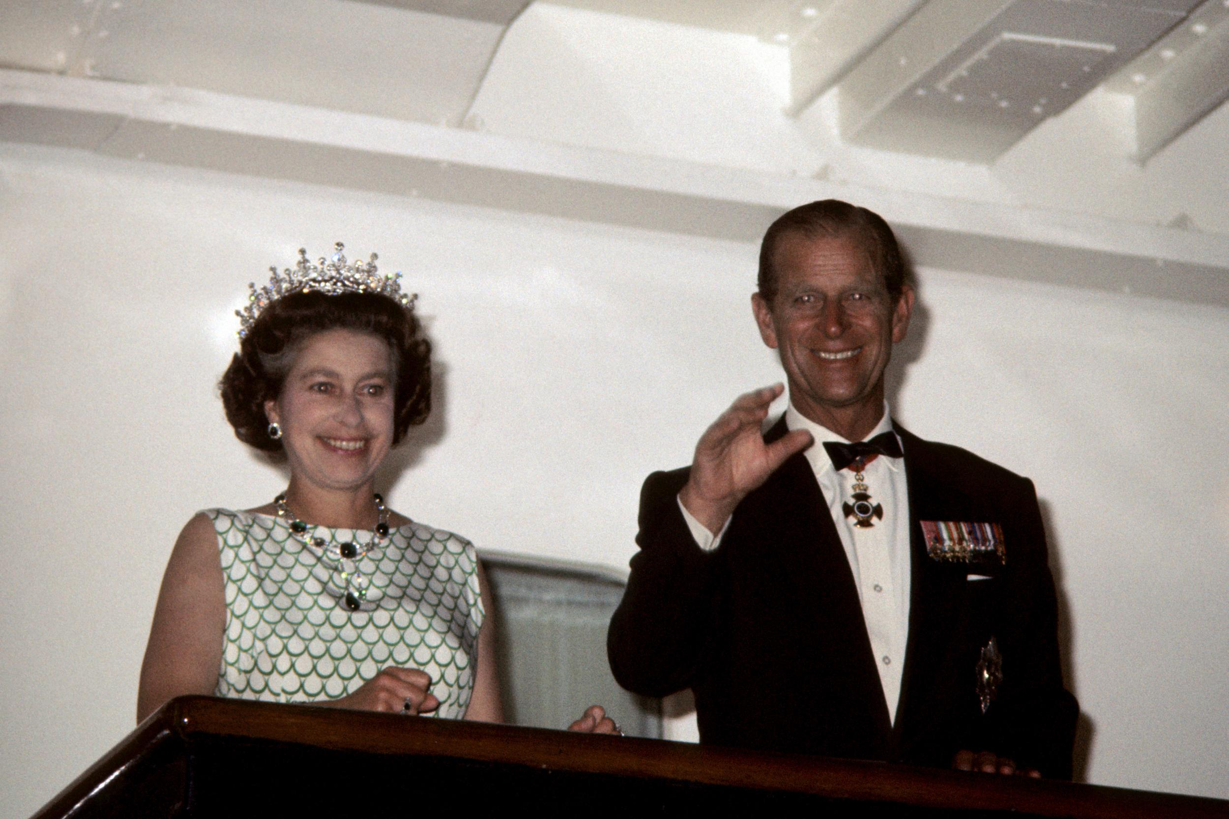 Queen Elizabeth II and the Duke of Edinburgh wave to the crowds from the Royal Yacht Britannia as it leaves Tortola in the Virgin Islands, during the Silver Jubilee tour of the Caribbean.