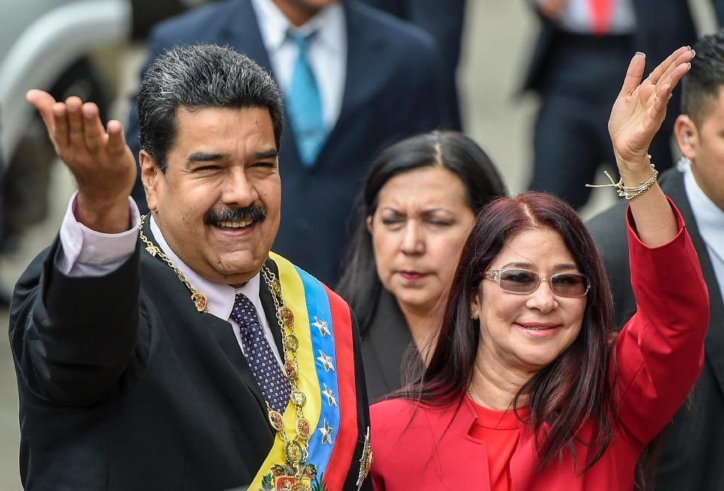 In this file photo taken on January 15, 2017 Venezuelan President Nicolas Maduro (L) and his wife, Cilia Flores wave to supporters (AFP Photo/JUAN BARRETO)