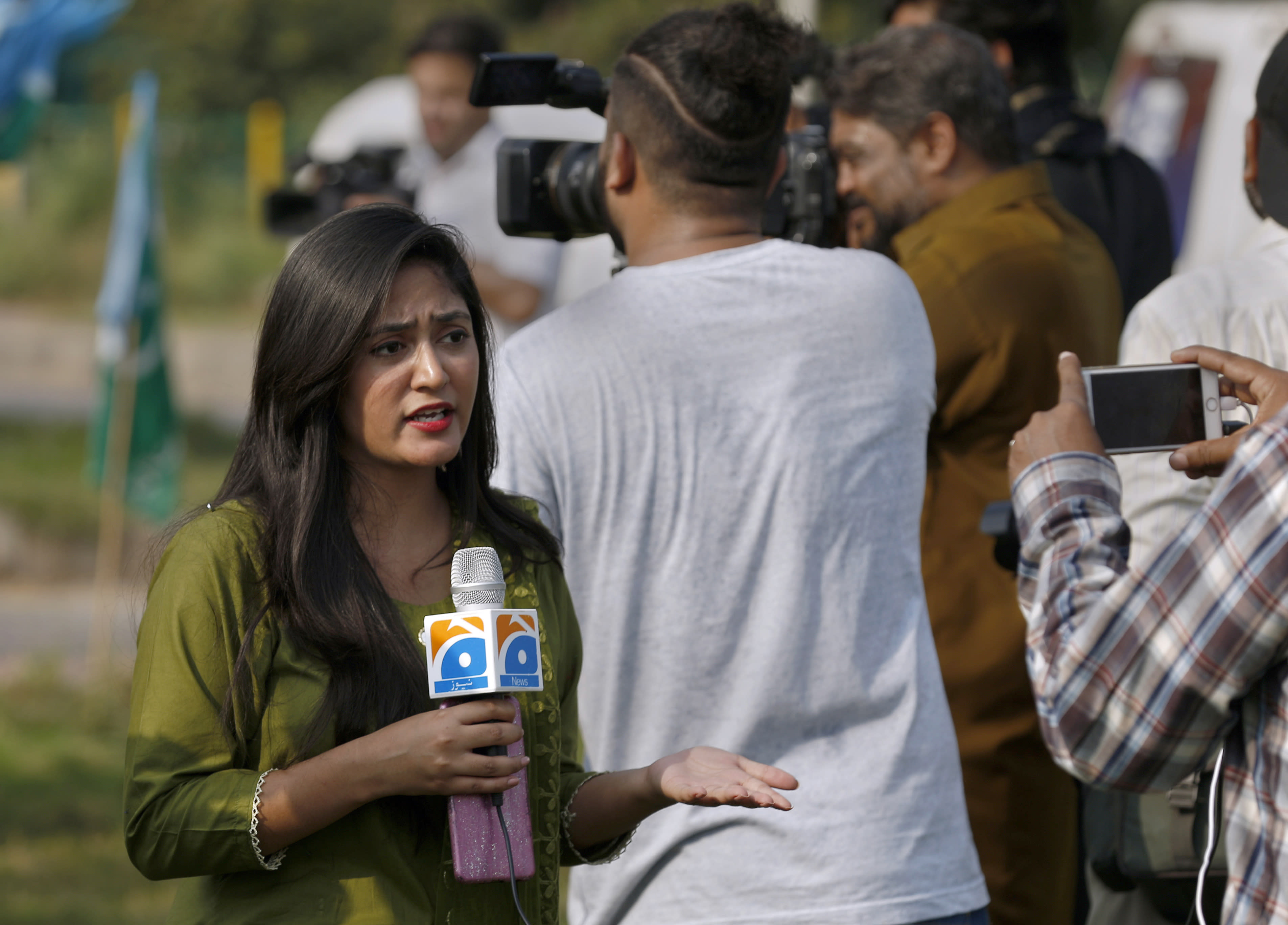 In this Friday, Sept. 11, 2020 photo, Alena Waqar, a female journalist from local tv channel Geo News, gives live reporting during a rally, in Islamabad, Pakistan. Social media attacks against Pakistan's women journalists have been vile and vicious, some threatening rape, others even threatening death and the culprits are most often allied to the ruling party, even prompting the Committee to Protect Journalists to issue a statement on Friday condemning the relentless attacks. (AP Photo/Anjum Naveed)
