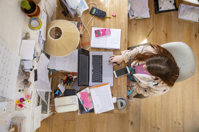 An overhead shot of a teenage Caucasian girl sitting at a desk at home studying. She is using a laptop and her desk is cluttered with books and such like.