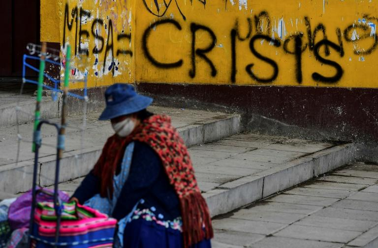 A woman is seen near a wall withagraffiti against presidential candidate Carlos Mesa, in El Alto, Bolivia, on October 17, 2020