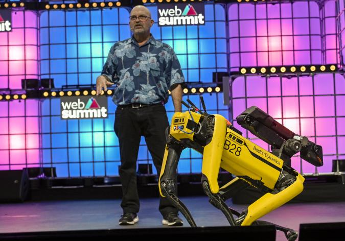 """LISBON, PORTUGAL - NOVEMBER 07: Marc Raibert, Founder & CEO, Boston Dynamics, speaks on """"Welcome to the future of mobile robots"""" and demonstrate their capability onstage with Spot, one of them at Center Stage of Web Summit in Altice Arena on November 07, 2019 in Lisbon, Portugal. Web Summit is an annual technology conference which brings together a variety of technology companies to discuss the future of industry. This year's event runs from November 4- 7 and is expected to attract around 70,000 participants.  (Photo by Horacio Villalobos/Corbis via Getty Images)"""