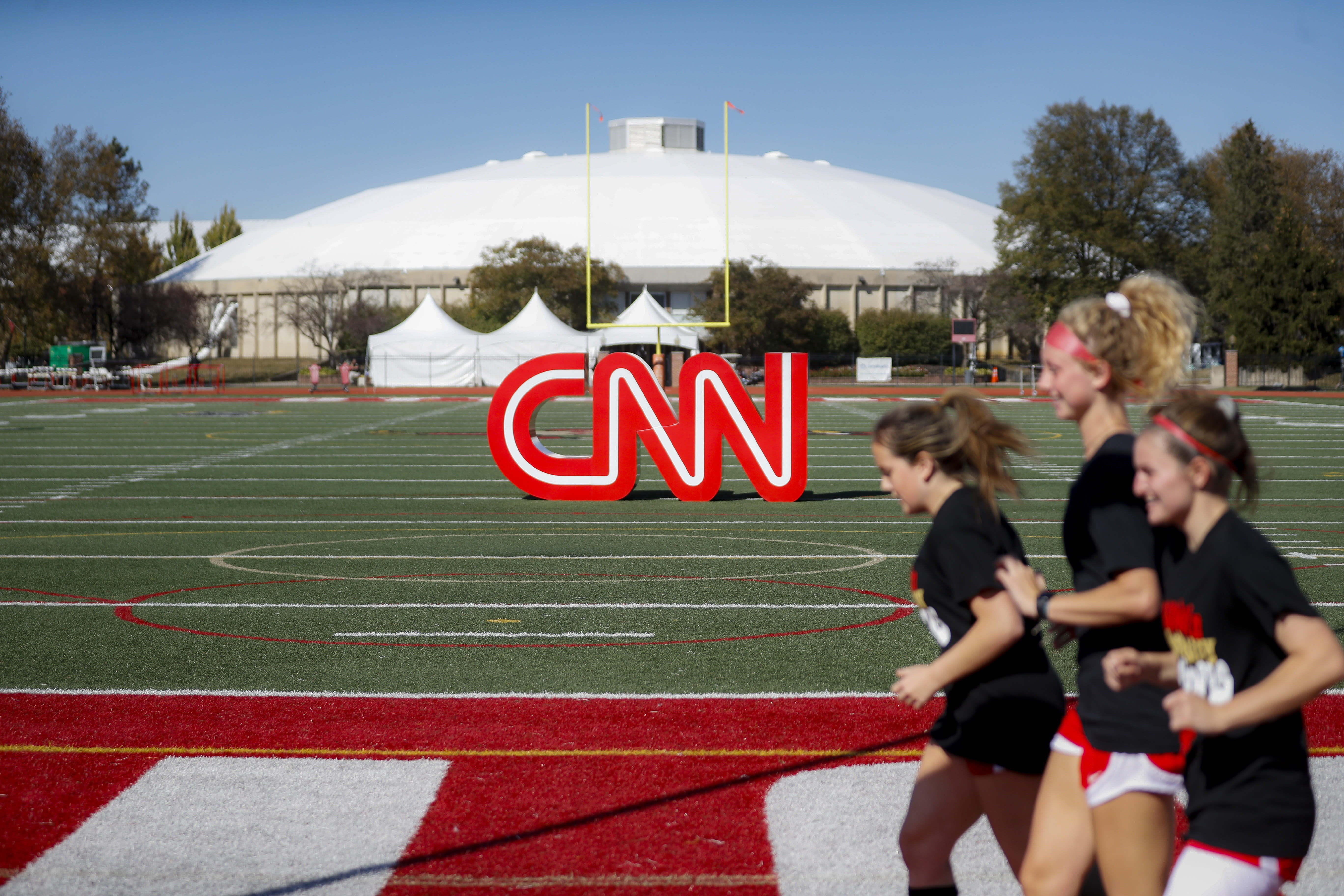 Student athletes pass a CNN sign on an athletic field outside the Clements Recreation Center where the CNN  New York Times will host the Democratic presidential primary debate at Otterbein University Monday Oct. 14 2019 in Westerville Ohio. (AP
