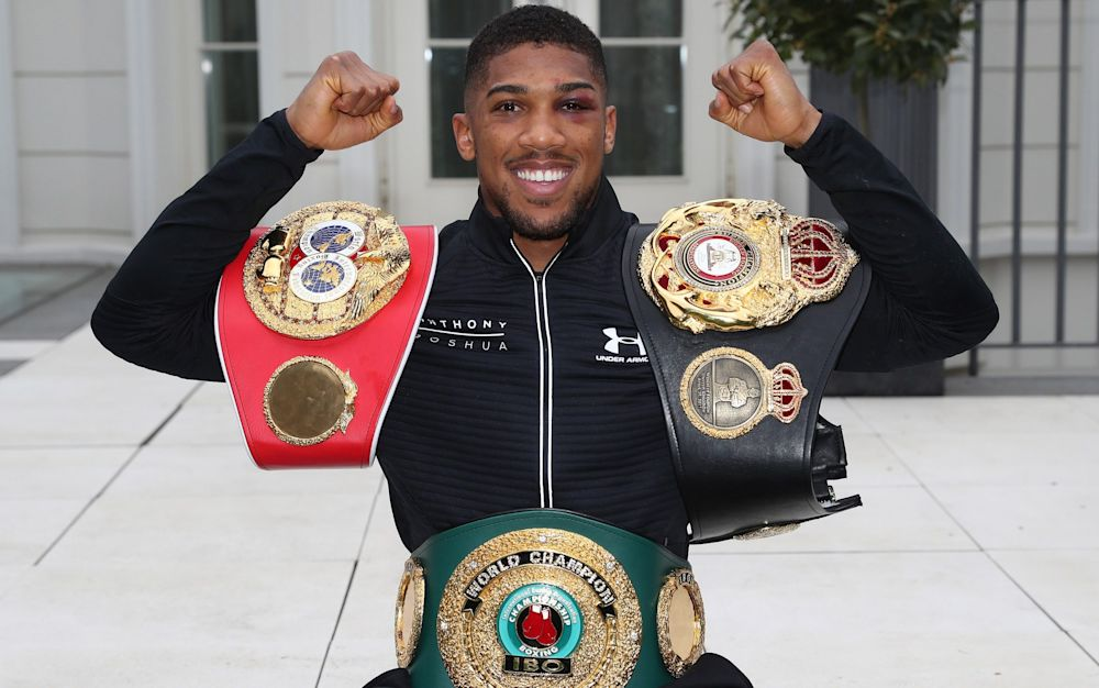 Anthony Joshua shows off his world heavyweight title belts the morning after defeating Wladimir Klitschko in a classic match at Wembley - LAWRENCE LUSTIG