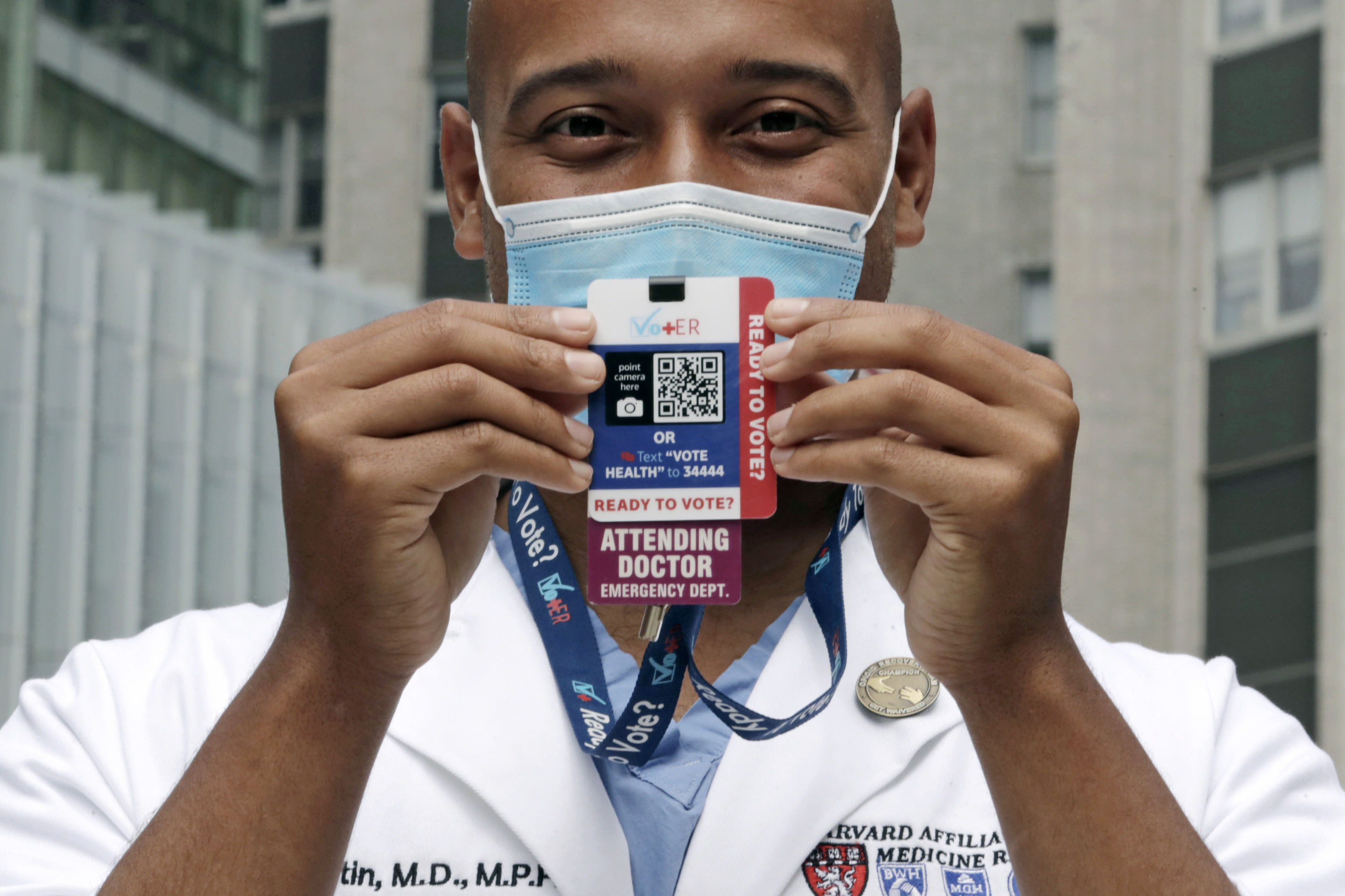 """Alister Martin, an emergency room doctor at Massachusetts General Hospital, holds up a voter information card he wears on his ID lanyard, which gives patients a Q-code and text link to help them register to vote, outside the hospital, Friday, Aug. 7, 2020, in Boston. Martin founded the organization """"VotER"""" to provide medical professionals voter registration resources for patients who are unregistered voters. (AP Photo/Charles Krupa)"""