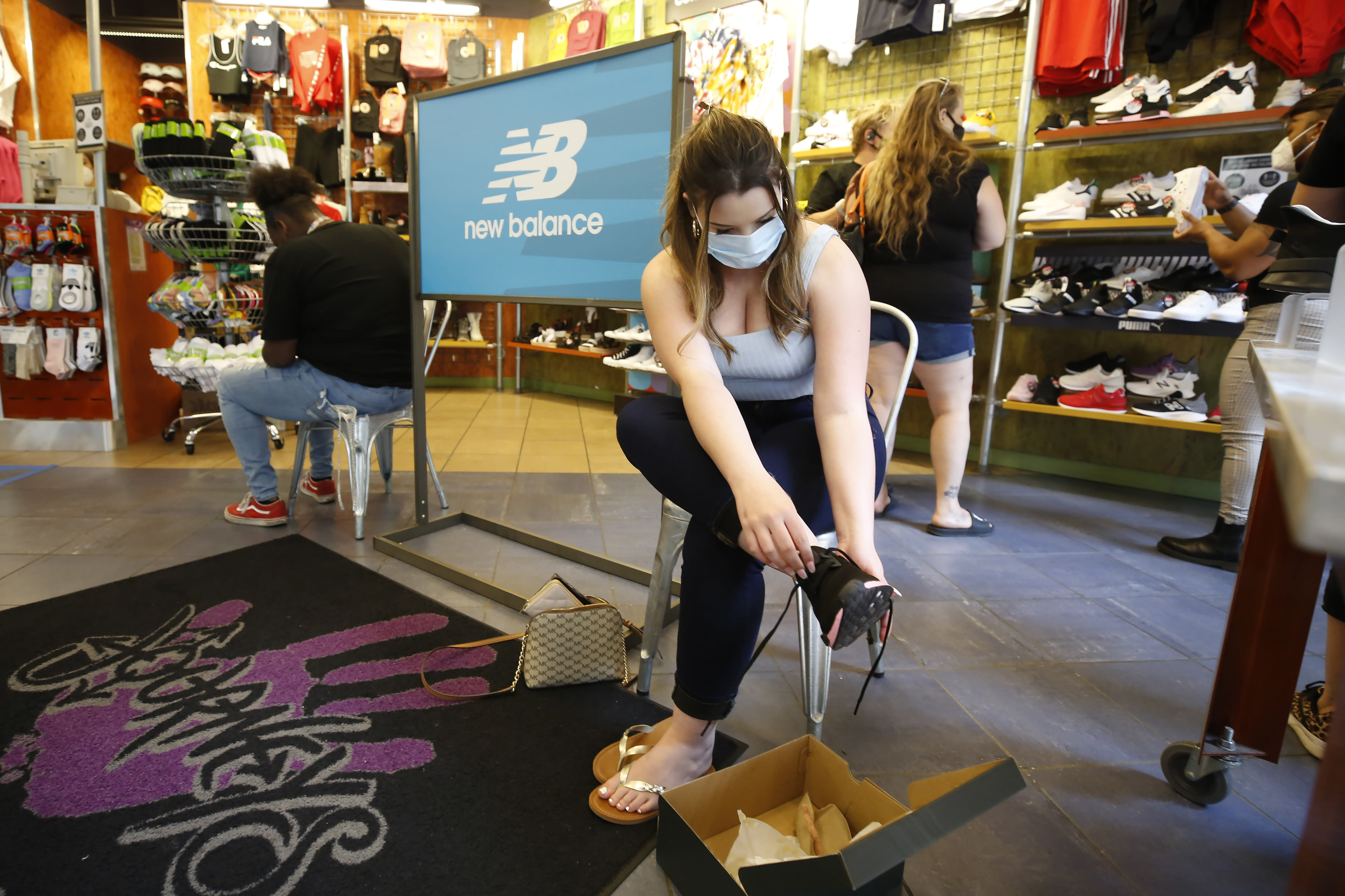 Allie Arredonodo, wears a face mask as she tries on shoes at Journey's shoe store in the Yuba Sutter Mall in Yuba City, Calif., Wednesday, May 6, 2020. Several dozen shoppers streamed into the first California mall to reopen Wednesday, despite Gov. Gavin Newsom's orders restraining businesses because of the coronavirus pandemic. (AP Photo/Rich Pedroncelli)