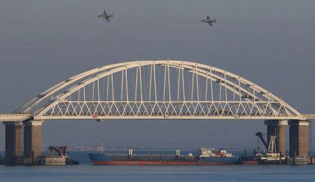 Russian jet fighters fly over a bridge connecting the Russian mainland with the Crimean Peninsula with a cargo ship beneath it after three Ukrainian navy vessels was stopped by Russia from entering the Sea of Azov via the Kerch Strait in the Black Sea