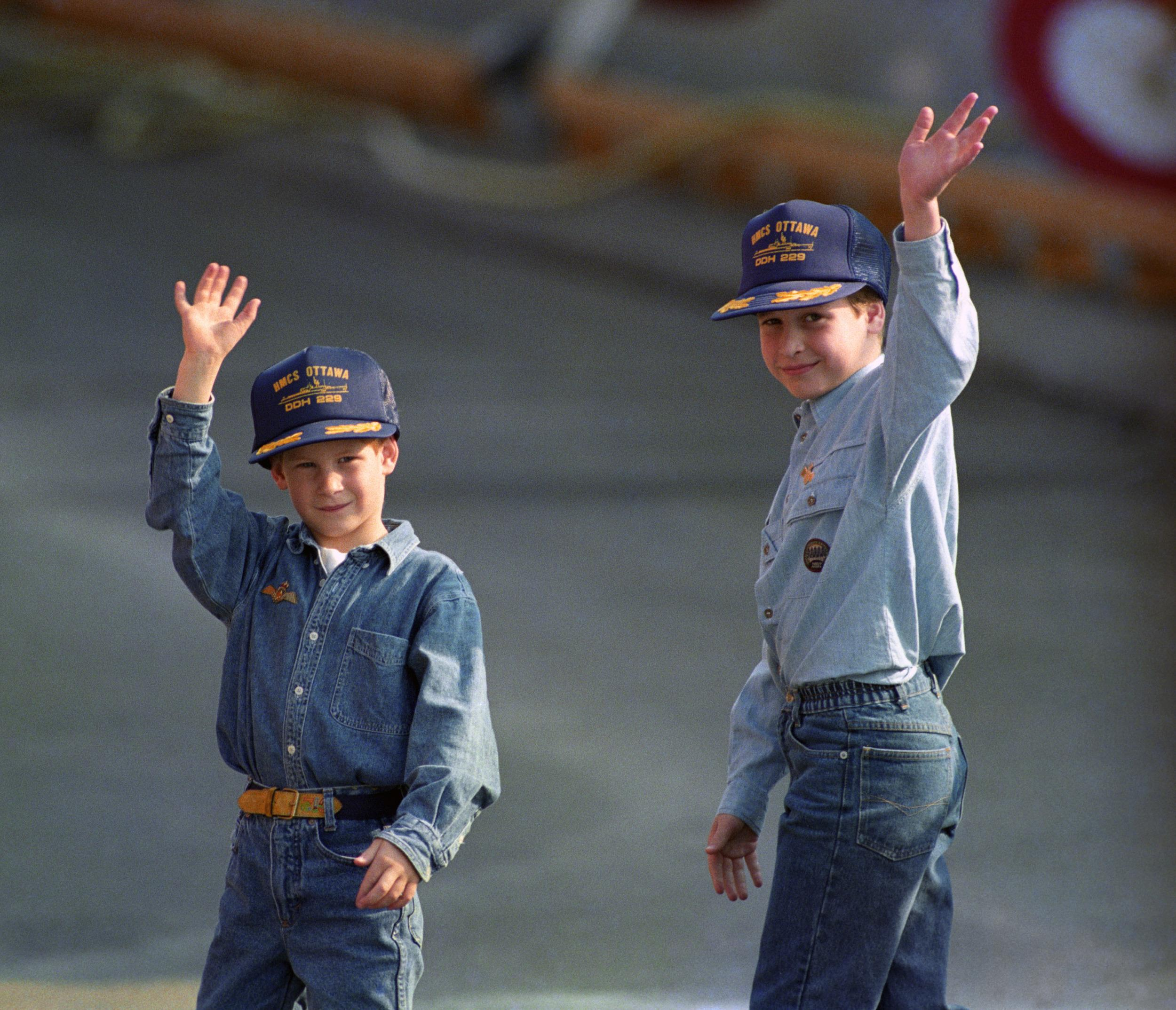 Prince William, 9, and his younger brother, Prince Harry, 7, wear baseball-style caps given to them by the crew of the Canadian frigate HMCS Ottowa after they toured the ship which is moored alongside the Royal Yacht Britannia on the Toronto waterfront.   (Photo by Martin Keene - PA Images/PA Images via Getty Images)