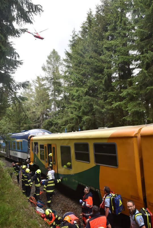 Rescuers and firefighters are seen working on a site of a train crash near Pernink