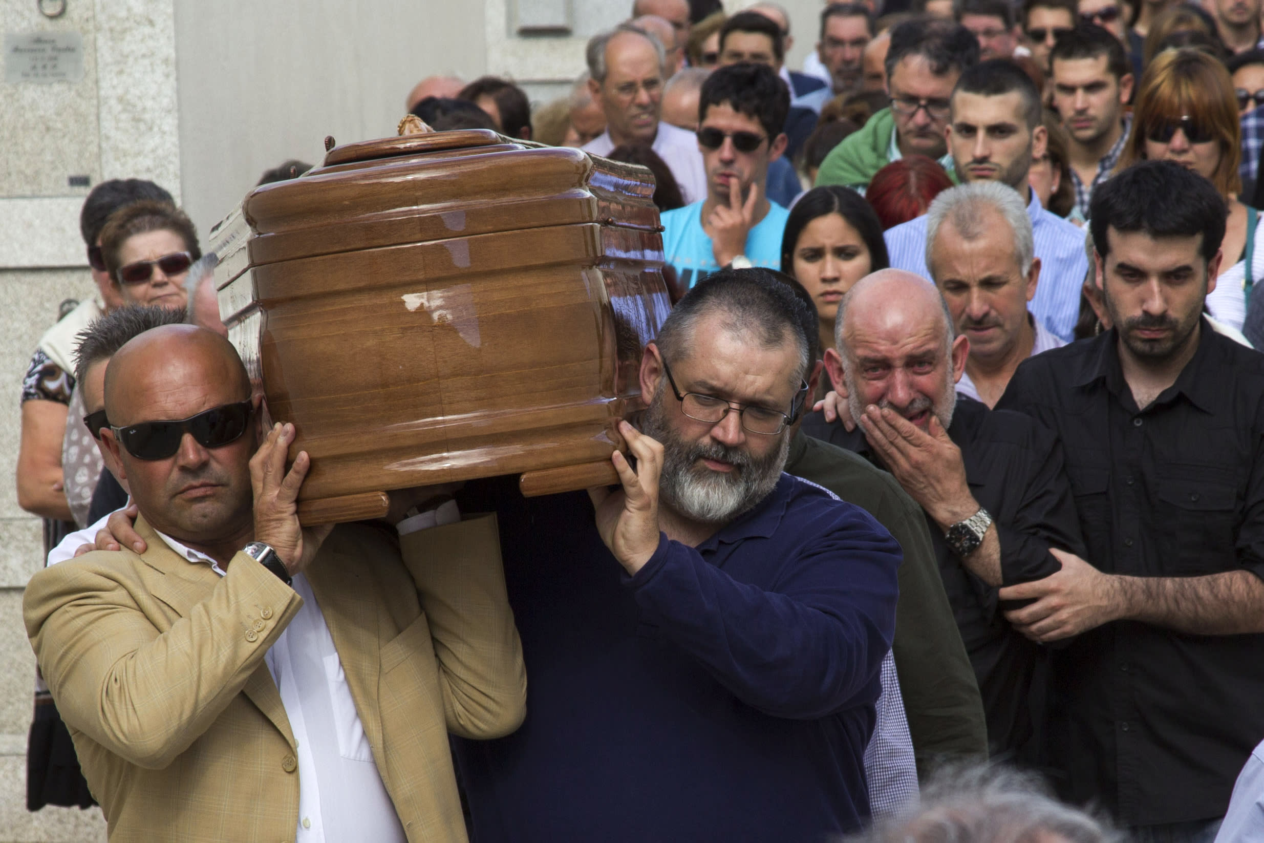 People carry the coffin of medical student Laura Naveiras Ferreiro, one of the train crash victim, during her funeral at the San Pedro de Visma cemetery in A Coruna, Spain, Saturday, July 27, 2013. Spain's interior minister Jorge Fernandez Diaz says the driver whose speeding train crashed, killing 78 people, is now being held on suspicion of negligent homicide. The Spanish train derailed at high speed Wednesday killing 78 and injuring dozens more. (AP Photo/Lalo R. Villar)