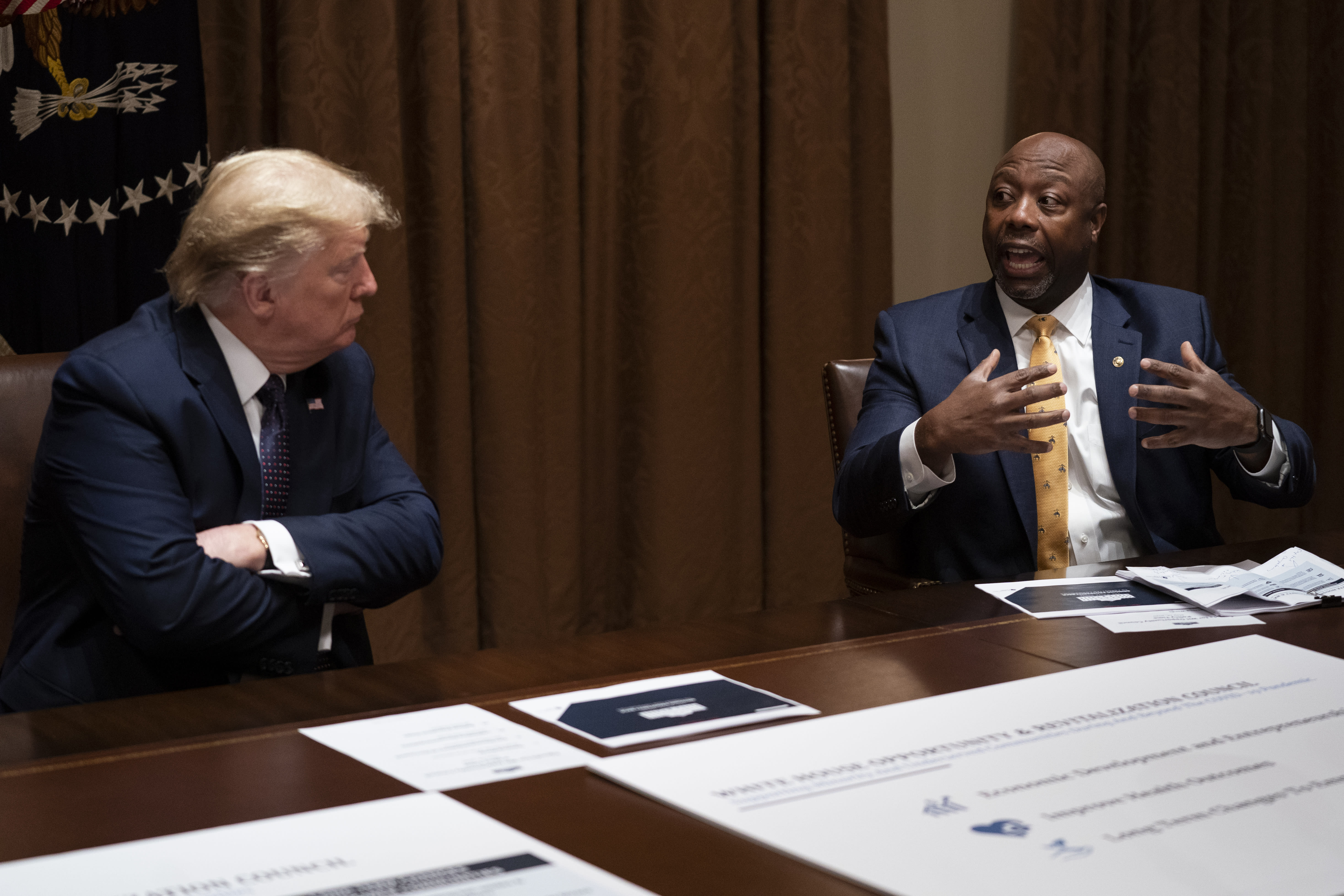 FILE - In this May 18, 2020, file photo, President Donald Trump listens as Sen. Tim Scott, R-S.C., speaks during a meeting on opportunity zones in the Cabinet Room of the White House in Washington. Initially reluctant to speak on race, Scott is now among the Republican Party's most prominent voices teaching his colleagues what it's like to be a Black man in America. (AP Photo/Evan Vucci, File)
