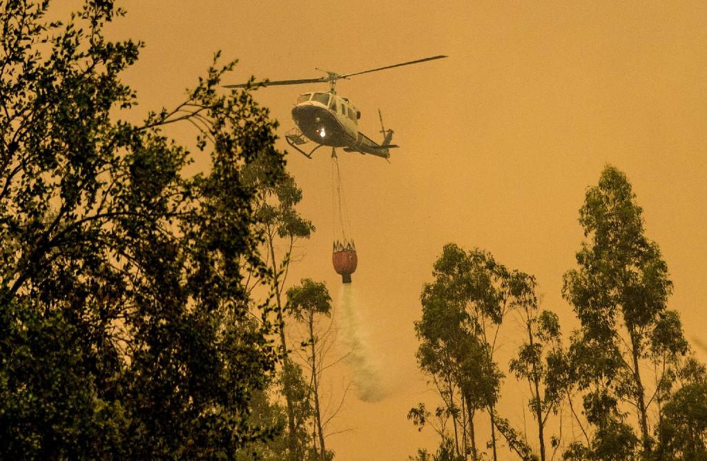 A firefighter helicopter helps try to put out a forest fire in Pumanque, 140 km south of Santiago on January 21, 2017
