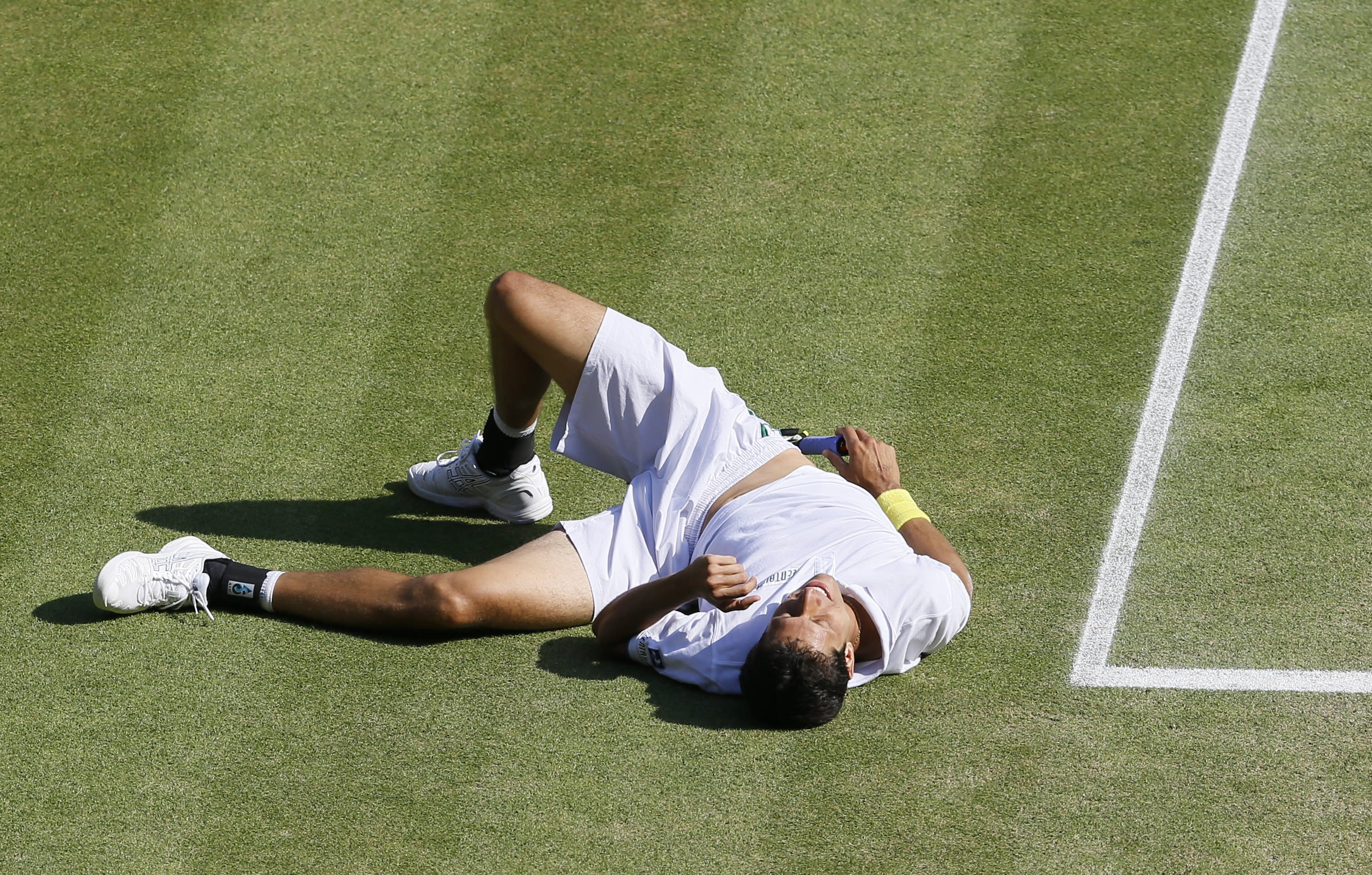 Marcelo Melo Brazil falls on the court as he as plays Bob Bryan of the United States and Mike Bryan of the United States during their Men's doubles final match at the All England Lawn Tennis Championships in Wimbledon, London, Saturday, July 6, 2013. (AP Photo/Kirsty Wigglesworth)
