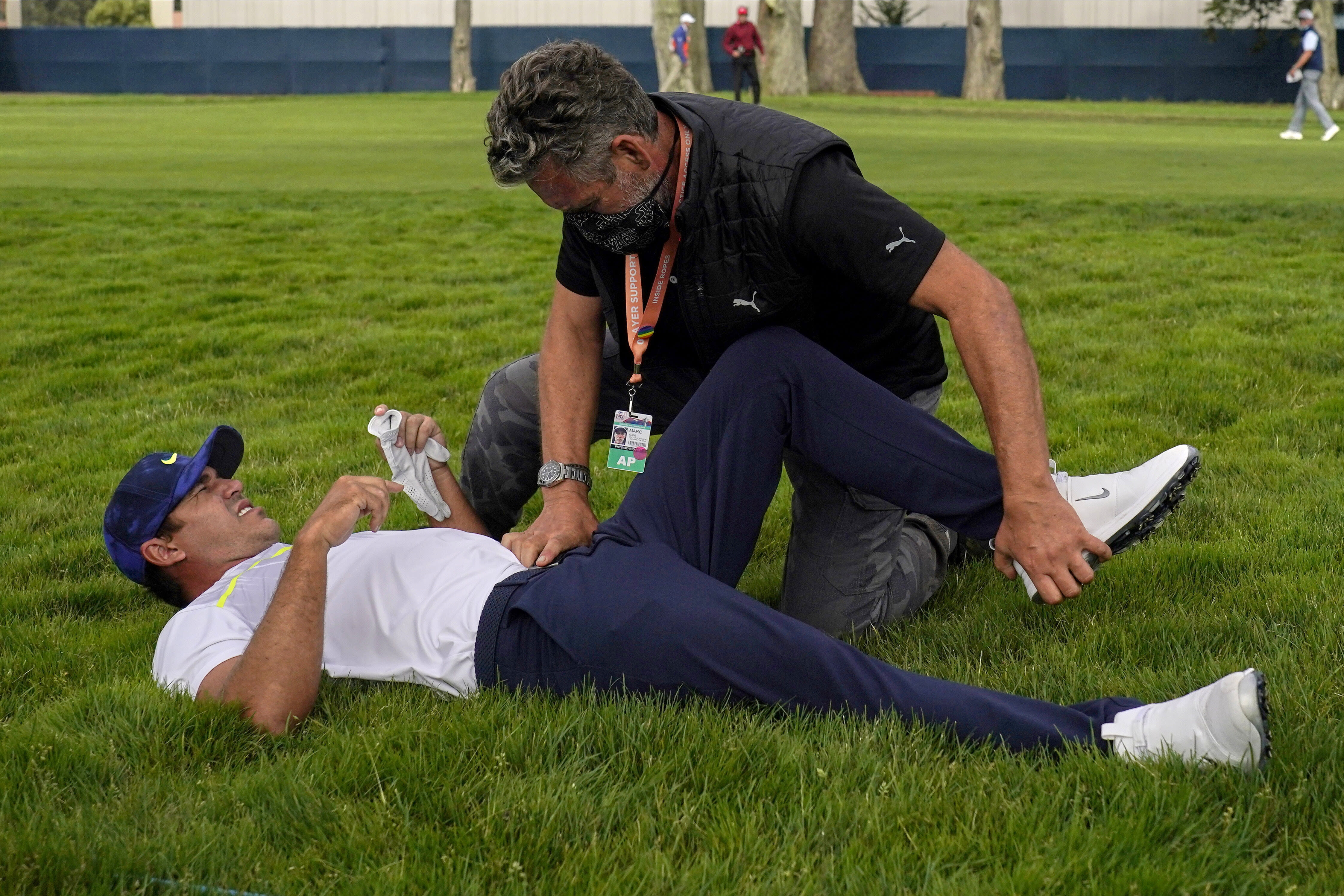 File-This Aug. 7, 2020, file photo shows Brooks Koepka getting treated for an injury on the 12th hole during the second round of the PGA Championship golf tournament at TPC Harding Park Friday, Aug. 7, 2020, in San Francisco. Koepka was out two months with a hip injury and returns this week at the CJ Cup at Shadow Creek in Las Vegas. (AP Photo/Jeff Chiu, File)
