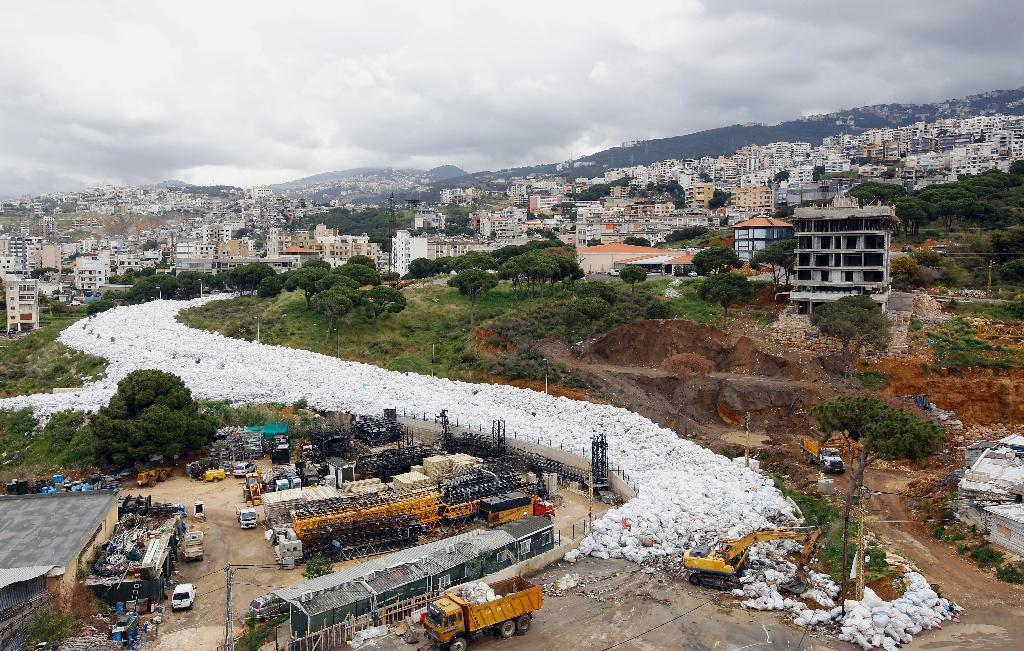 Trucks are seen next to piles of rubbish in Jdeideh, a Beirut suburb, ahead of moving it to the country's largest landfill of Naameh, just south of the Lebanese capital, on March 20, 2016 (AFP Photo/Anwar Amro)