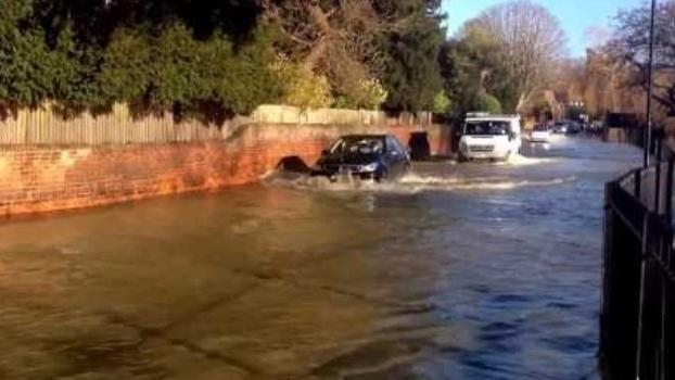 Cyclist Leads the Way on Flooded Surrey Road