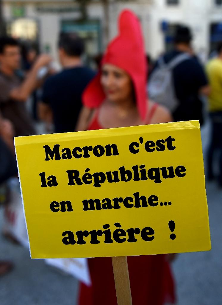 """A demonstrator holds a placard reading """"Macron that's the republic on the move... backwards!"""" during a protest against the French government's planned labour law reforms (AFP Photo/BORIS HORVAT)"""