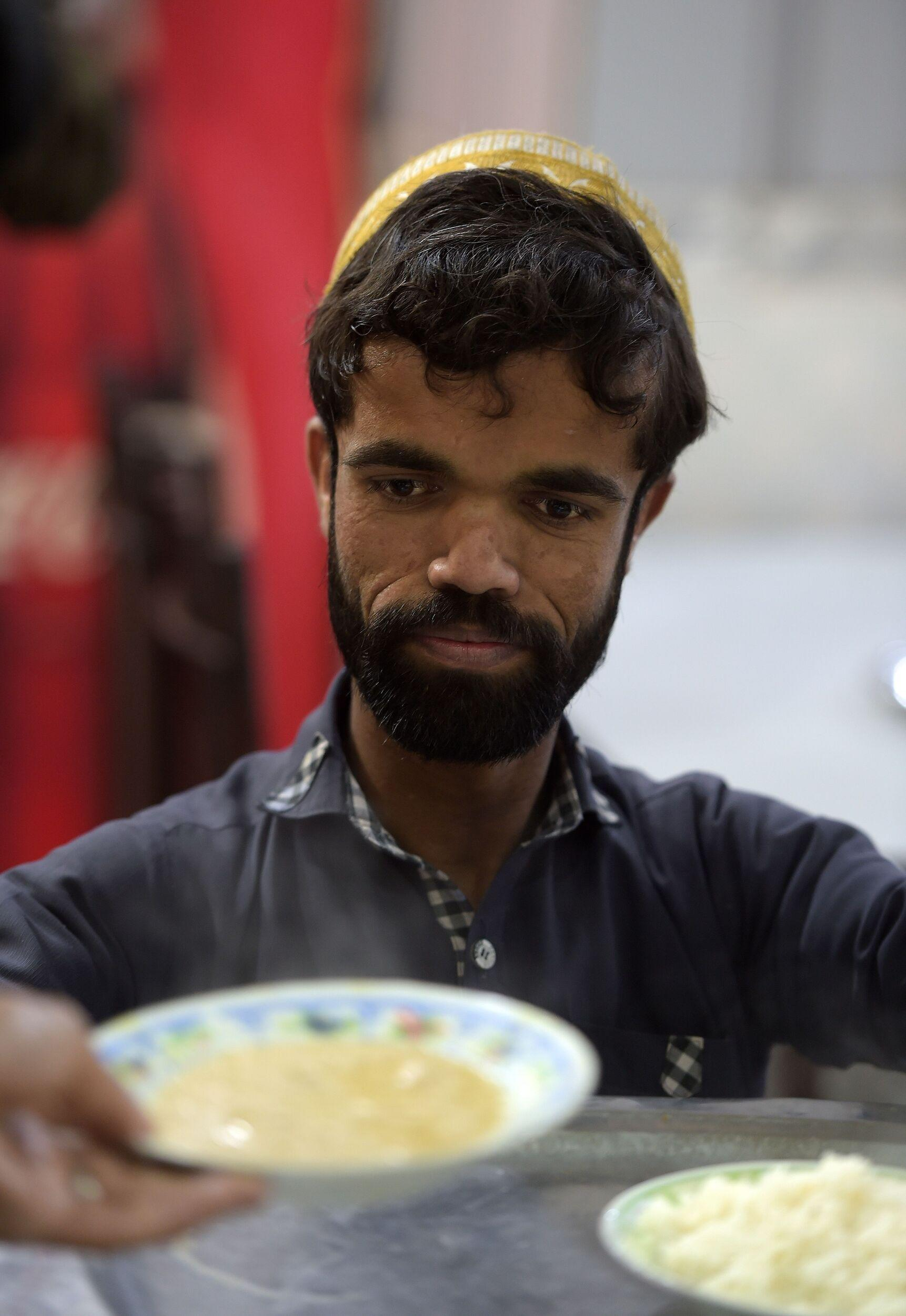 In this picture taken on February 22, 2019, Rozi Khan, a 25-year-old Pakistani waiter who resembles US actor Peter Dinklage, prepares to serve food to customers at Dilbar Hotel in Rawalpindi. - Rozi Khan had never heard of the Game of Thrones -- or its hugely popular character Tyrion Lannister -- until his striking resemblance to the dwarf anti-hero got heads turning at home. (Photo by AAMIR QURESHI / AFP) / To go with PAKISTAN-LIFESTYLE-TELEVISION-ENTERTAINMENT        (Photo credit should read AAMIR QURESHI/AFP/Getty Images)