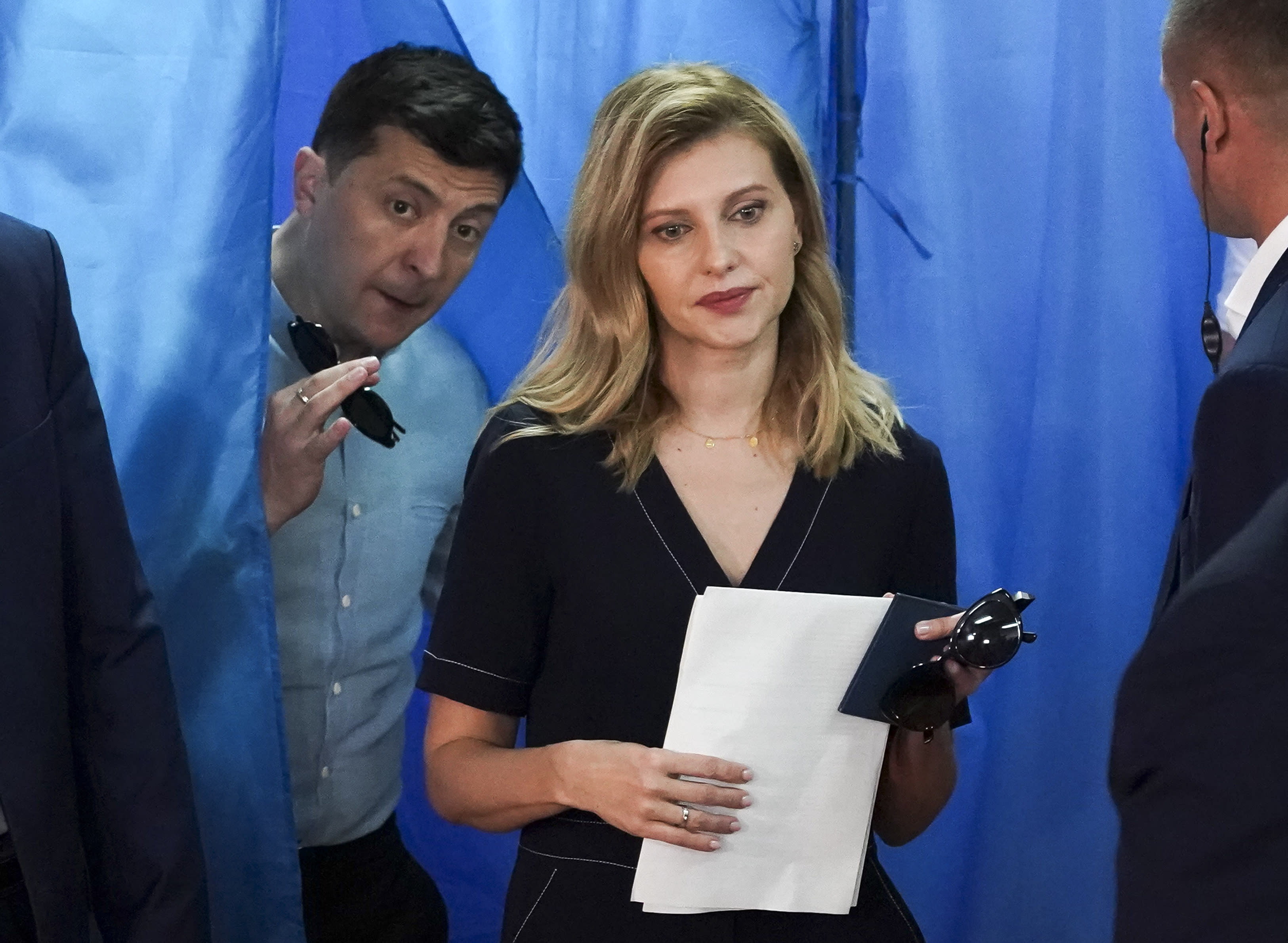 Ukrainian President Volodymyr Zelenskiy, ,left, and his wife Olena Zelenska leave a booth at a polling station during a parliamentary election in Kiev, Ukraine, Sunday, July 21, 2019. Ukrainians are voting in an early parliamentary election in which the new party of President Volodymyr Zelenskiy is set to take the largest share of votes. (AP Photo/Evgeniy Maloletka)