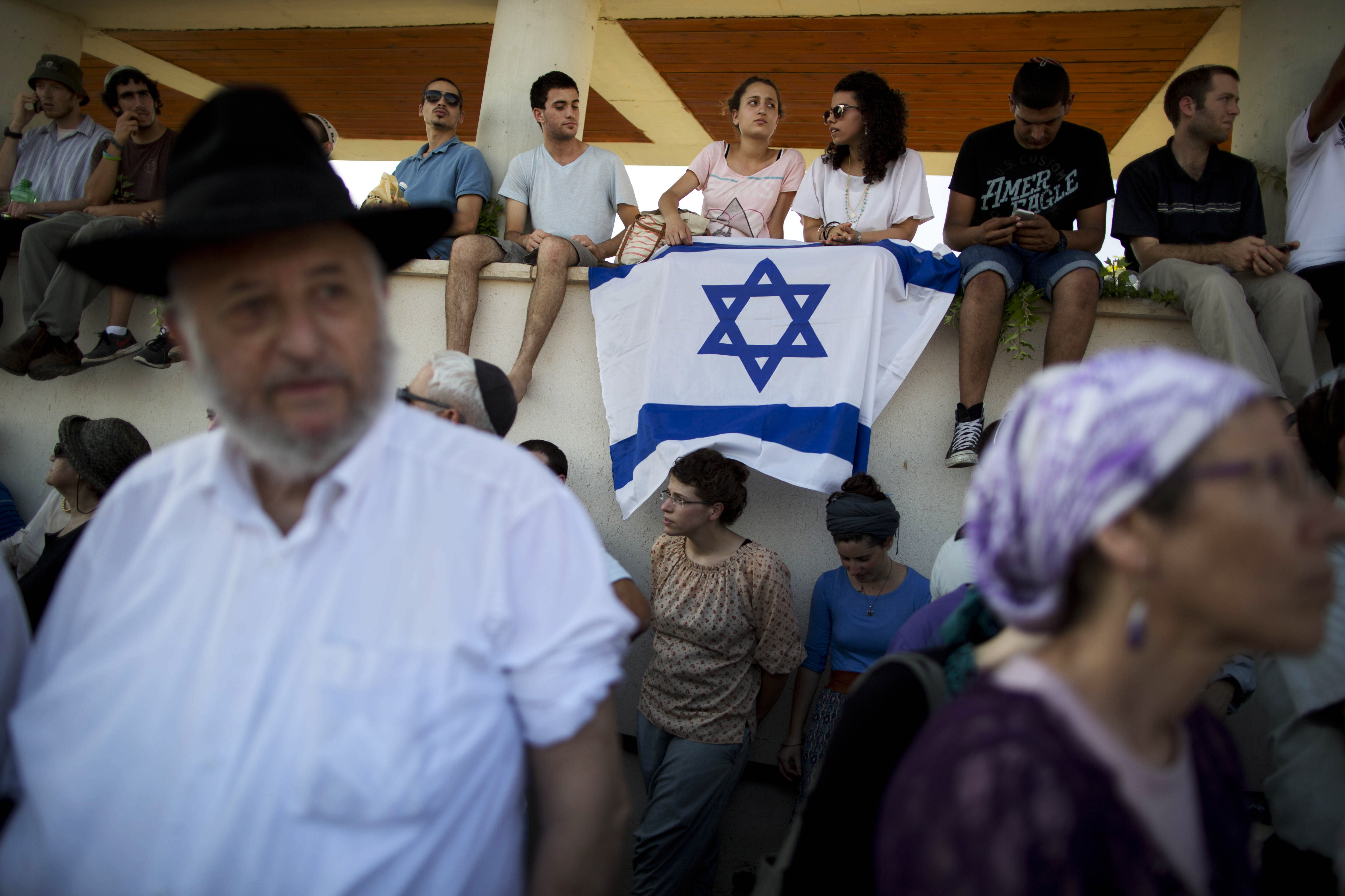 """FILE - In this July 1, 2014 file photo, Israelis attend the funeral of three Israeli teenagers, Eyal Yifrah, 19, Gilad Shaar, 16, and Naftali Fraenkel, a 16-year-old with dual Israeli-American citizenship, in the Israeli town of Modiin. HBO's new docudrama series about the killings of four Israeli and Palestinian teenagers, which set off a cascade of events leading to the 2014 Gaza war, is set to air next week and is likely to reopen wounds on both sides of the conflict. """"Our Boys,"""" co-created by Palestinian and Israeli filmmakers, presents a dramatized rendition of the chaotic events of that June following the abduction of three Israeli teens in the West Bank. (AP Photo/Oded Balilty, File)"""