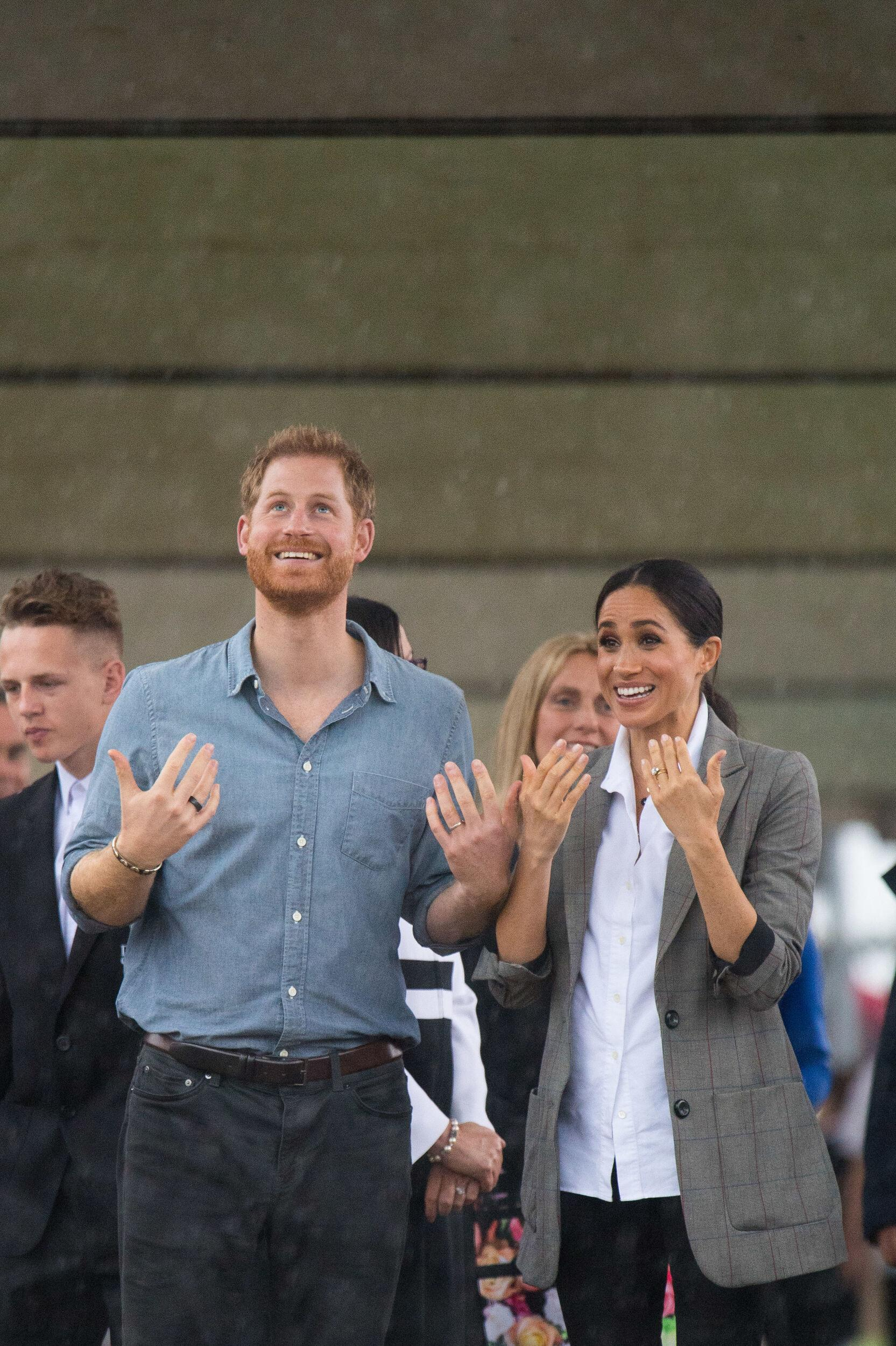 The Duke and Duchess of Sussex look out at a heavy downpour of rain during a visit to Clontarf Foundation and Girls Academy in Dubbo, New South Wales, on the second day of the royal couple's visit to Australia.