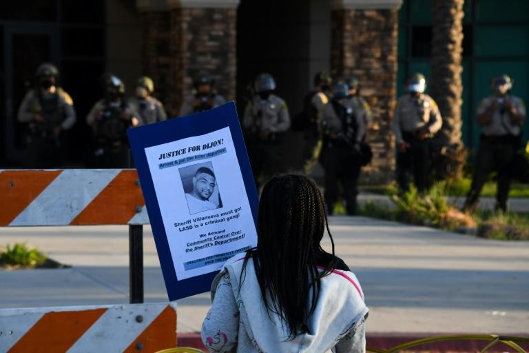 A young girl holds a placard and stands facing Sheriff's deputies in riot gear in front of the South L.A. Sheriff's Station on September 1, 2020 in Los Angeles, as protestors demand justice for Dijon Kizzee who was shot and killed the previous day by Los Angeles Sheriff's Deputies
