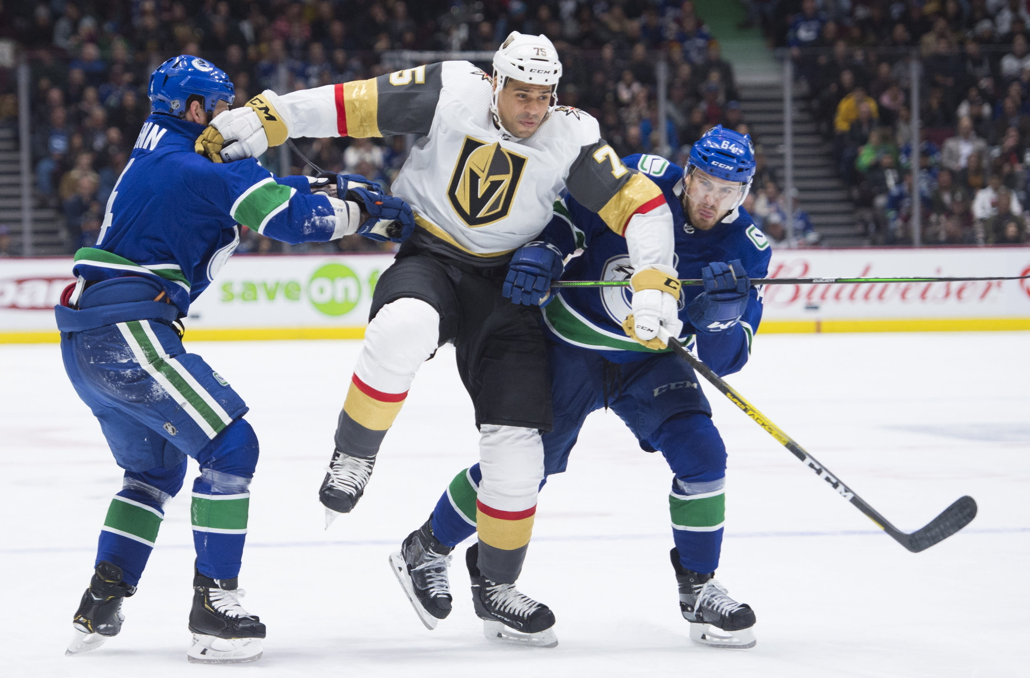 FILE - In this Dec 19, 2019, file photo, Vegas Golden Knights right wing Ryan Reaves (75) jumps to get past Vancouver Canucks defenseman Jordie Benn, left, and center Tyler Motte (64) during the third period of an NHL hockey game in Vancouver, British Columbia. The NHL ditched divisional playoffs to go back to the old-school format for its summer postseason and still ended up with all division rivals facing off in the second round. It's the Golden Knights against the Canucks in the Pacific series (Jonathan Hayward/The Canadian Press via AP, File)