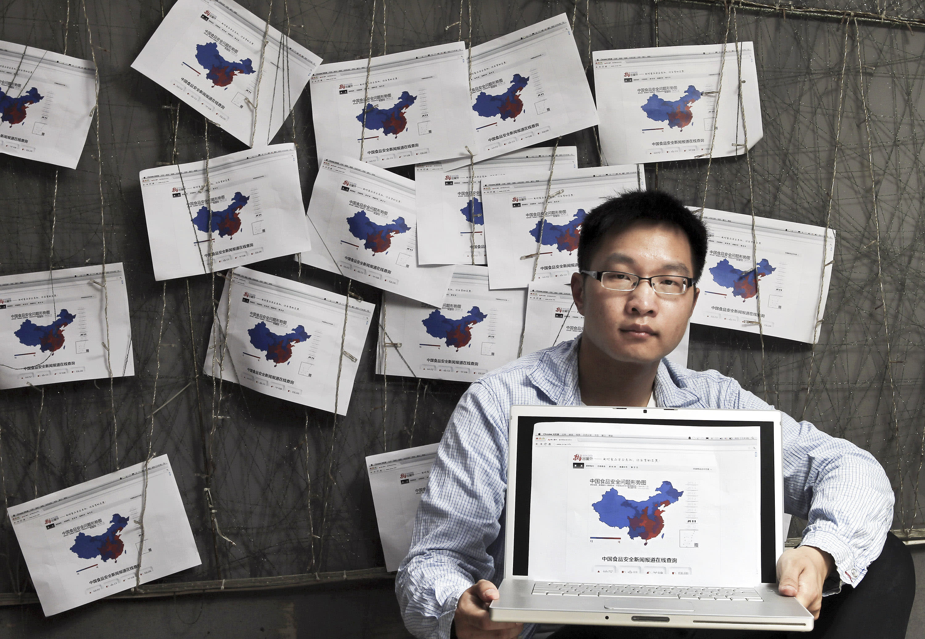 "In this photo taken on May 3, 2012, Wu Heng, a Shanghai grad student, poses with his web design titled: ""Zhichuchuangwai,"" or ""Throw it Out the Window,"" a site giving daily news feeds about the latest food scandals, that underscores the deep anger in China over the country's persistent food safety problems to the publics, in Shanghai, China. (AP Photo) CHINA OUT"