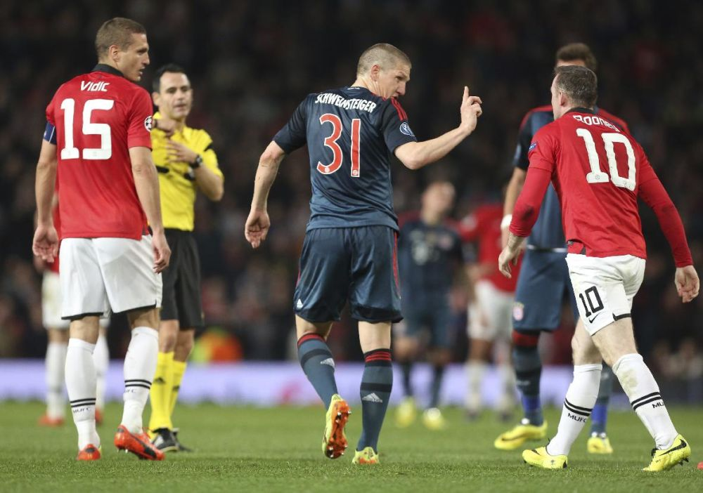Bayern's Bastian Schweinsteiger, center, argues with Manchester United's Wayne Rooney, after he was sent off the field by referee Carlos Velasco Carballo from Spain, second left, during the Champions League quarterfinal first leg soccer match between Manchester United and Bayern Munich at Old Trafford Stadium, Manchester, England, Tuesday, April 1, 2014