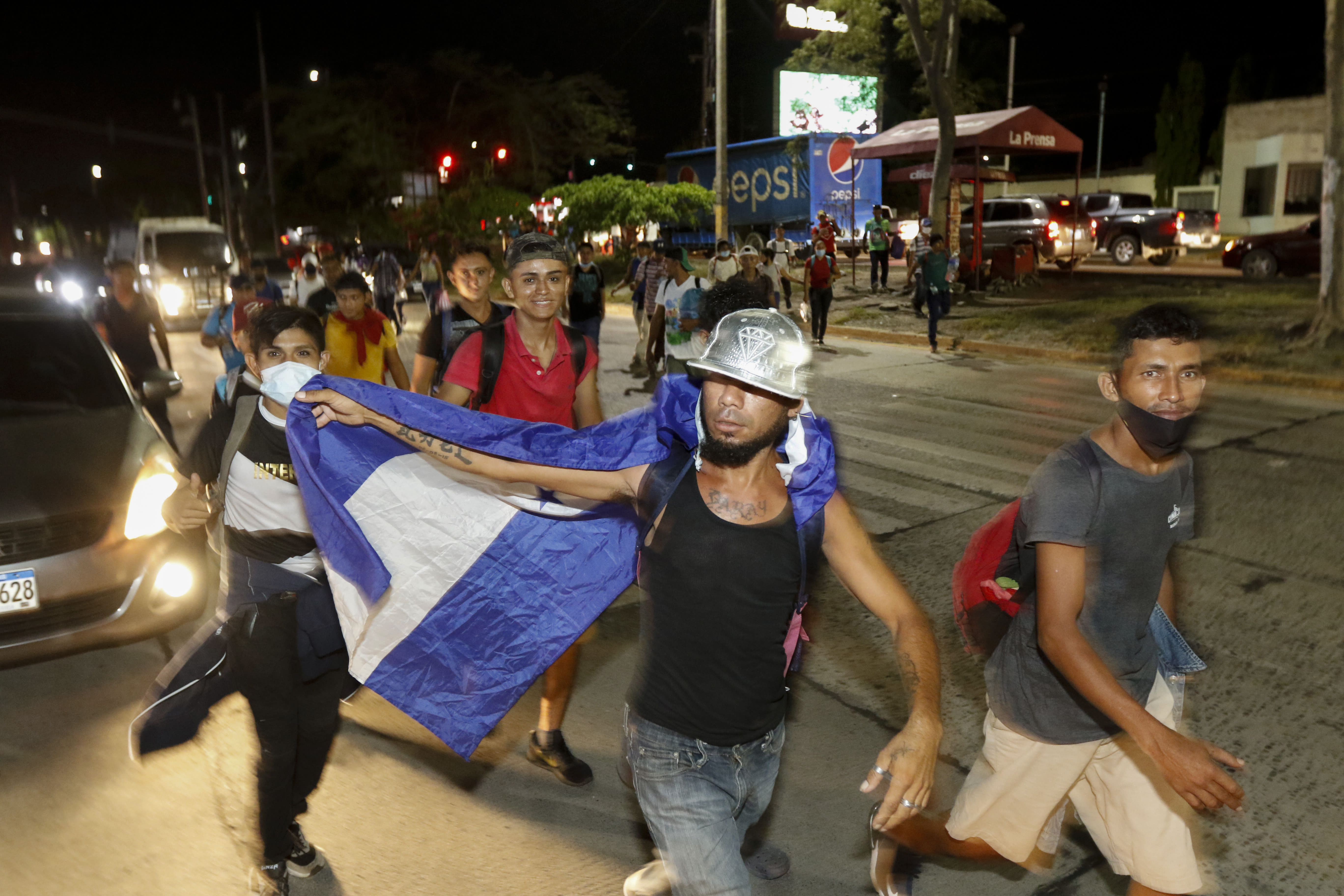Migrants walk along a highway in hopes of reaching the distant United States, in San Pedro Sula, Honduras, Wednesday, Sept. 30, 2020. Hundreds of migrants have begun walking from this northern Honduras city toward the Guatemala border testing a well-trod migration route now in times of the new coronavirus. (AP Photo)