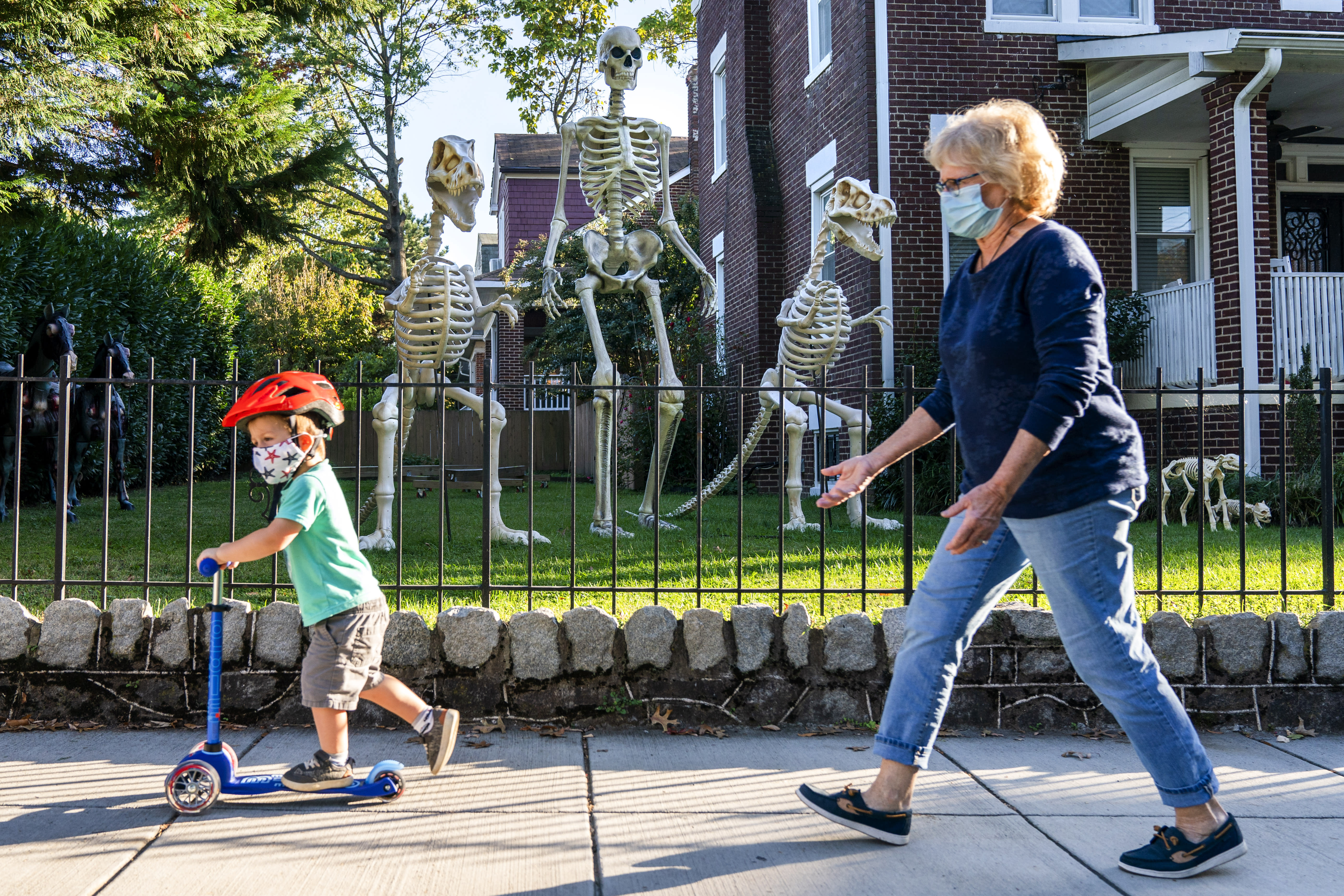 Sam McNamara, 3, of Washington, left, followed by his grandmother, scoots by a yard decorated with giant skeletons, both human and dinosaur, Wednesday, Oct. 14, 2020, in advance celebration of Halloween in Washington. (AP Photo/Jacquelyn Martin)
