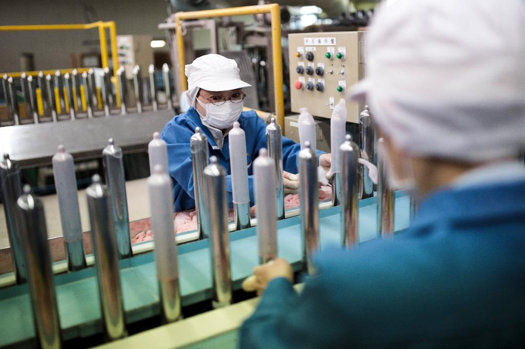 Workers at Japan's Sagami Rubber Industries perform quality tests for randomly picked condoms at the company's testing site in Atsugi, Kanagawa prefecture (AFP Photo/Behrouz MEHRI)