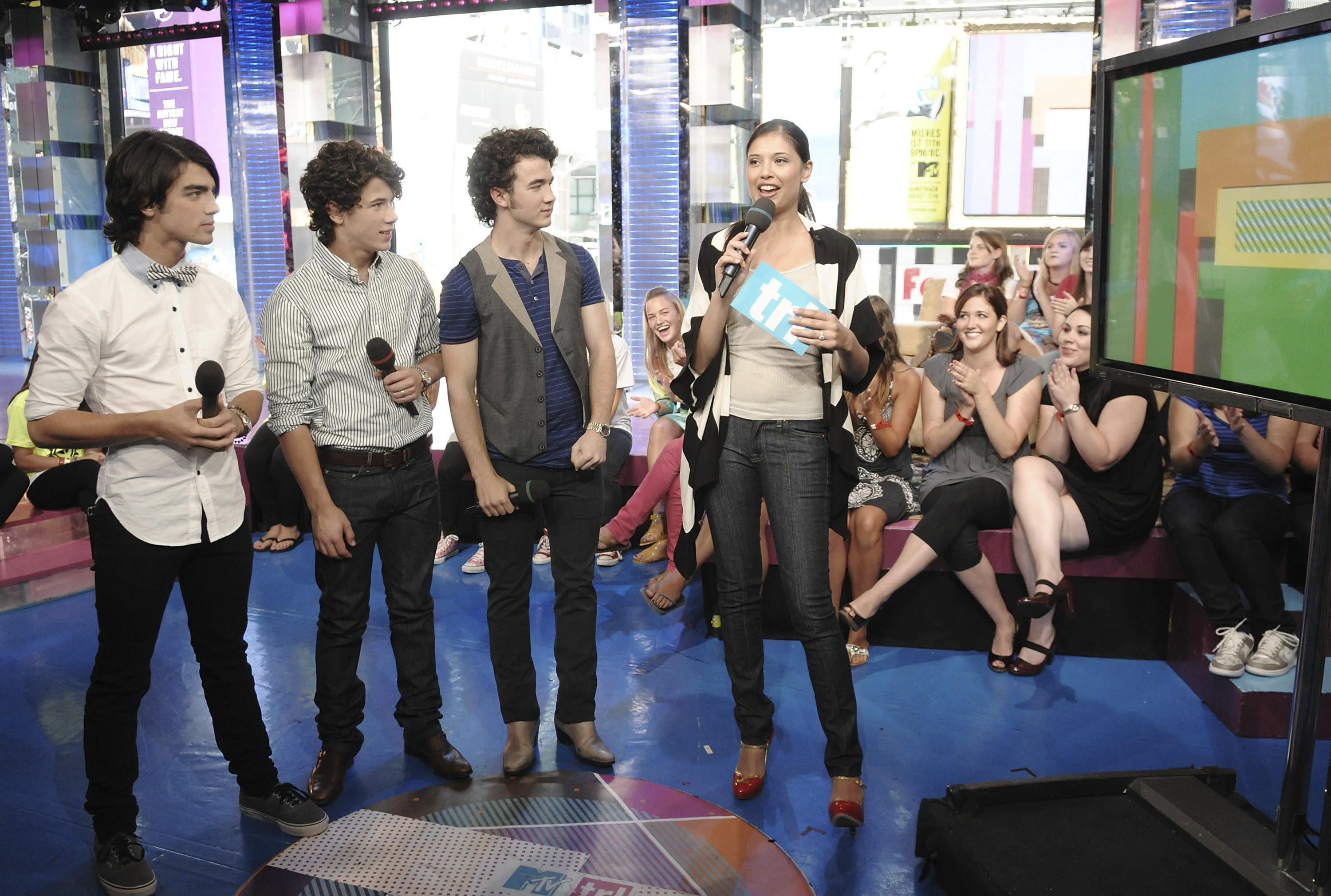 """FILE - The Jonas Brothers, from left, Joe, Nick and Kevin, chat with VJ Lyndsey Rodrigues during a co-hosting appearance on MTV's """"Total Request Live"""" on Aug. 11, 2008, in New York. CBS News is rebuilding MTV's old studio as its headquarters for election night. The network is installing giant touchscreens and """"augmented reality"""" displays for the big political night and says it will provide extra roominess to put on a television show in the COVID-19 era. (AP Photo/Evan Agostini, File)"""