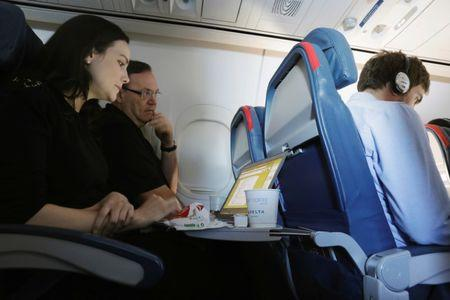 A woman uses her laptop on a flight out of JFK International Airport in New York