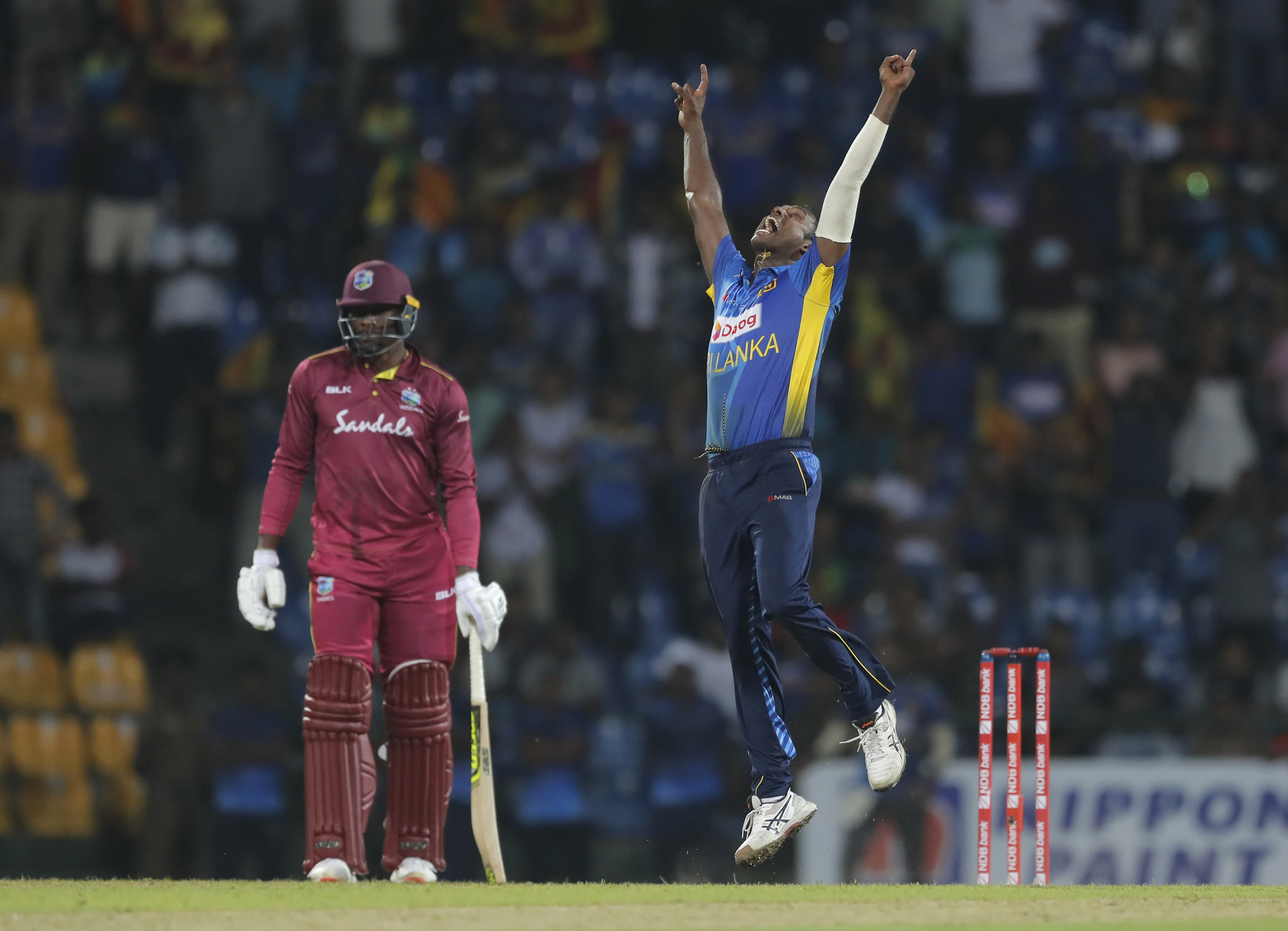 Sri Lanka's Angelo Mathews celebrates his team's six runs victory over West Indies in the third one day international cricket match as Sheldon Cottrell watches in Pallekele, Sri Lanka, Sunday, March 1, 2020. (AP Photo/Eranga Jayawardena)