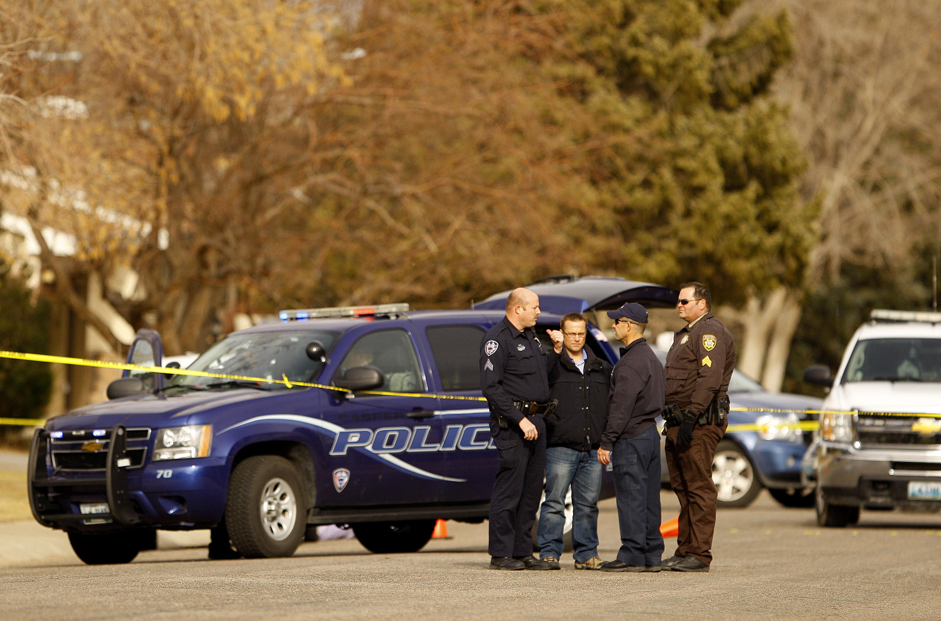 Police investigate the scene of a homicide in front of a house on Hawthorne Ave. in Casper on Friday, Nov. 30, 2012, in Casper, Wyo. The body of the victim was visible by neighbors for several hours. A man wielding a sharp-edged weapon killed one person in this Casper neighborhood Friday before killing a male teacher and himself in front of students in a community college classroom, causing a campus-wide lockdown as authorities tried to piece together what happened. (AP Photo/Dan Cepeda, Casper Star-Tribune) MANDATORY CREDIT; TRIB.COM