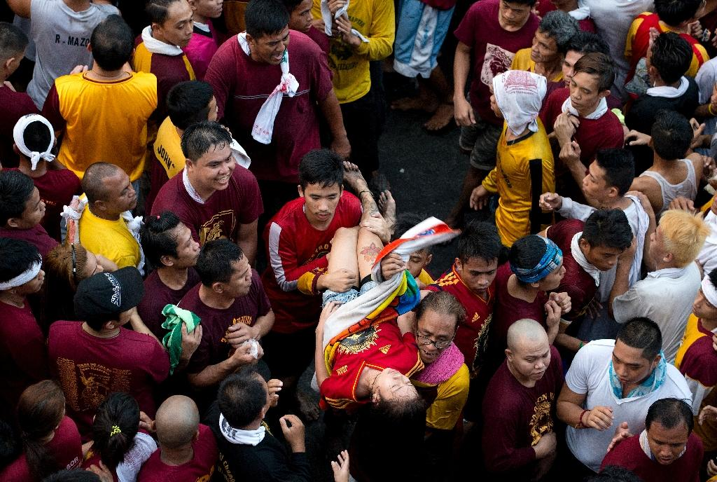 A female devotee is carried away after collapsing during an annual religious procession with the religious icon of the Black Nazarene in Manila on January 9, 2016 (AFP Photo/Noel Celis)