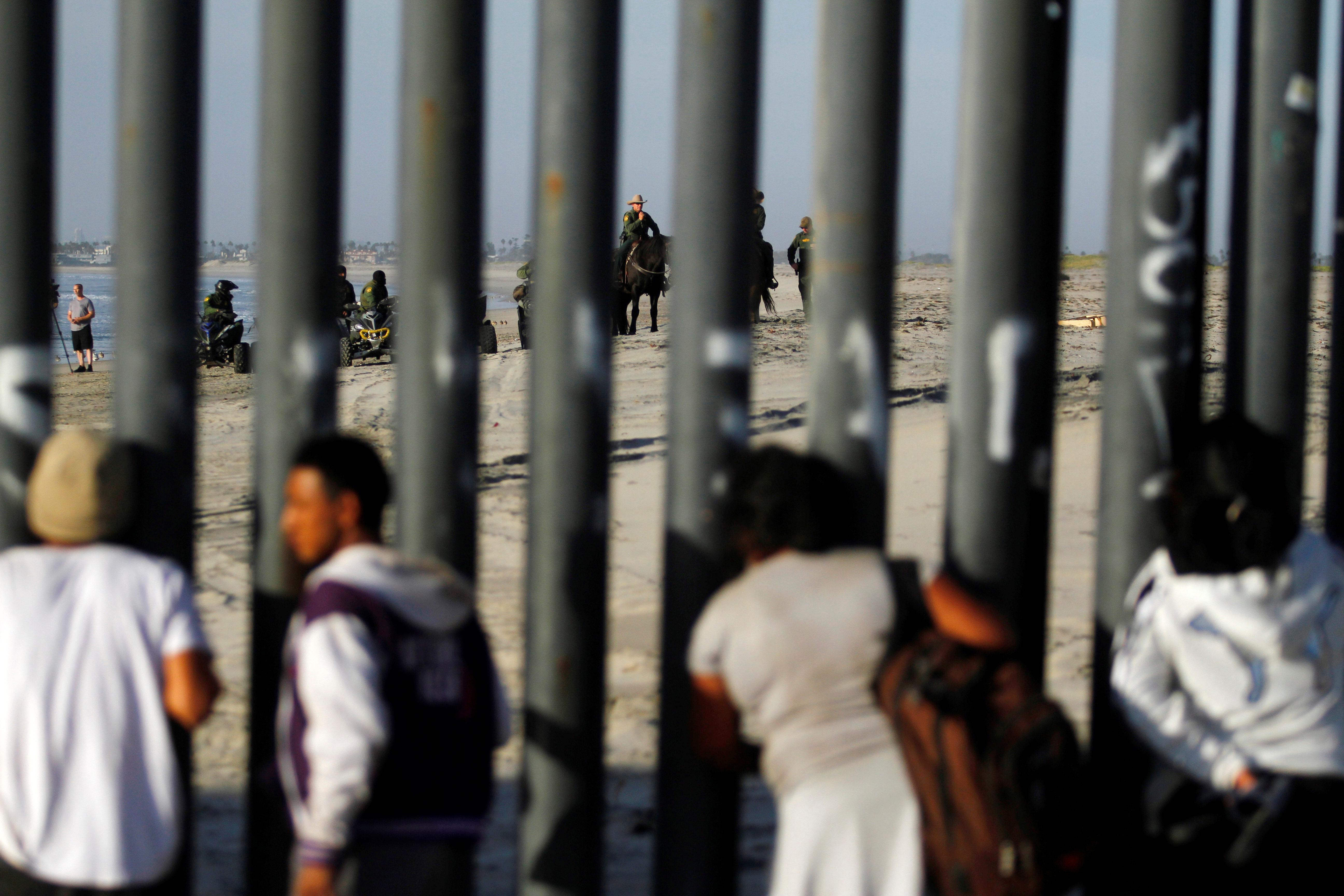 <p>Migrants, part of a caravan of thousands trying to reach the U.S., look at U.S. border patrol through the border fence between Mexico and the United States, after arriving in Tijuana, Mexico, Nov. 13, 2018. (Photo: Jorge Duenes/Reuters) </p>