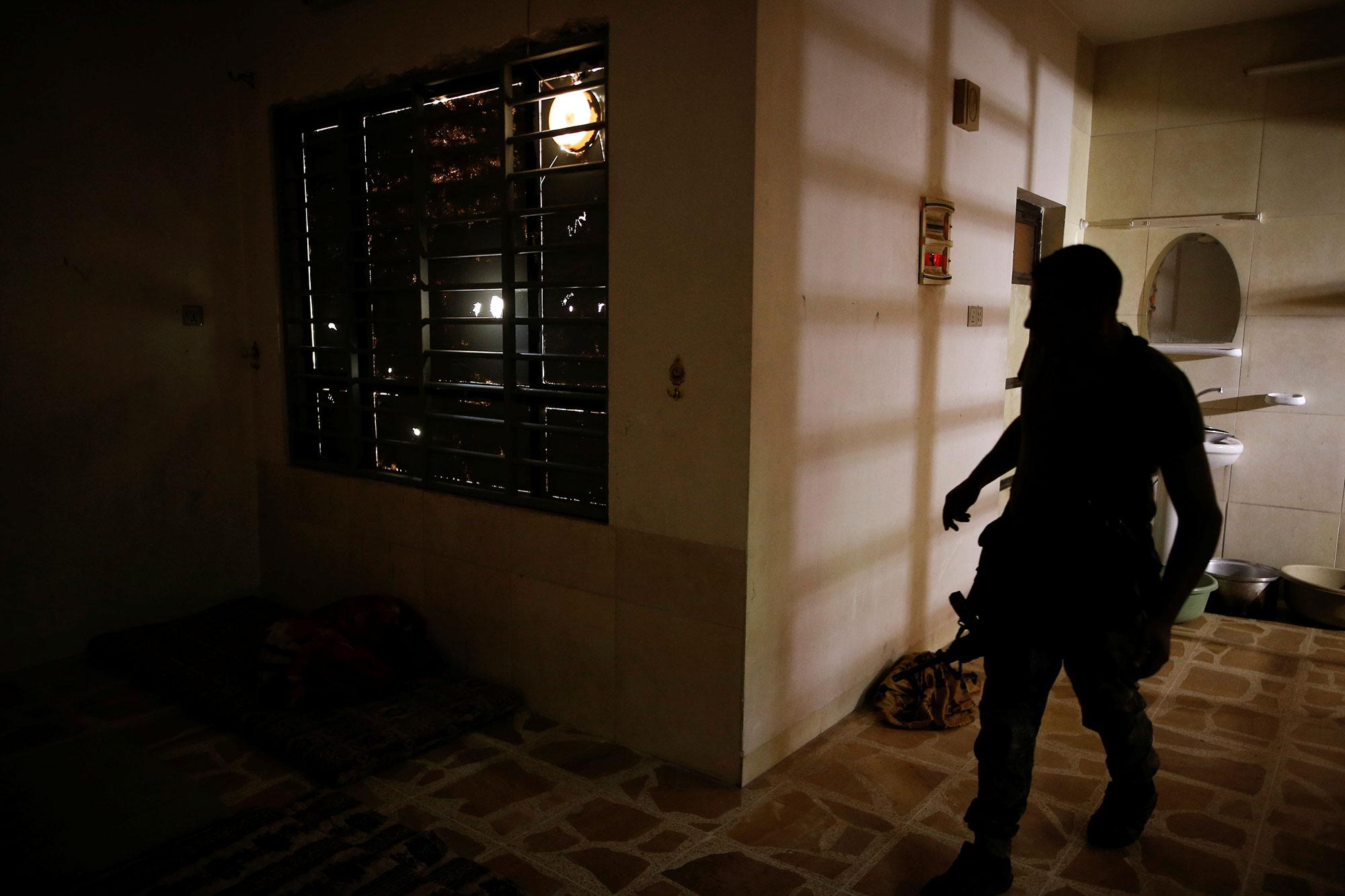 <p>A member of the Iraqi Army's 9th Armoured Division inspects a room used as a cell for women inside a compound used as a prison by Islamic State militants in the 17 Tamuz (July 17) district, in western Mosul, Iraq, June 6, 2017. (Alkis Konstantinidis/Reuters) </p>