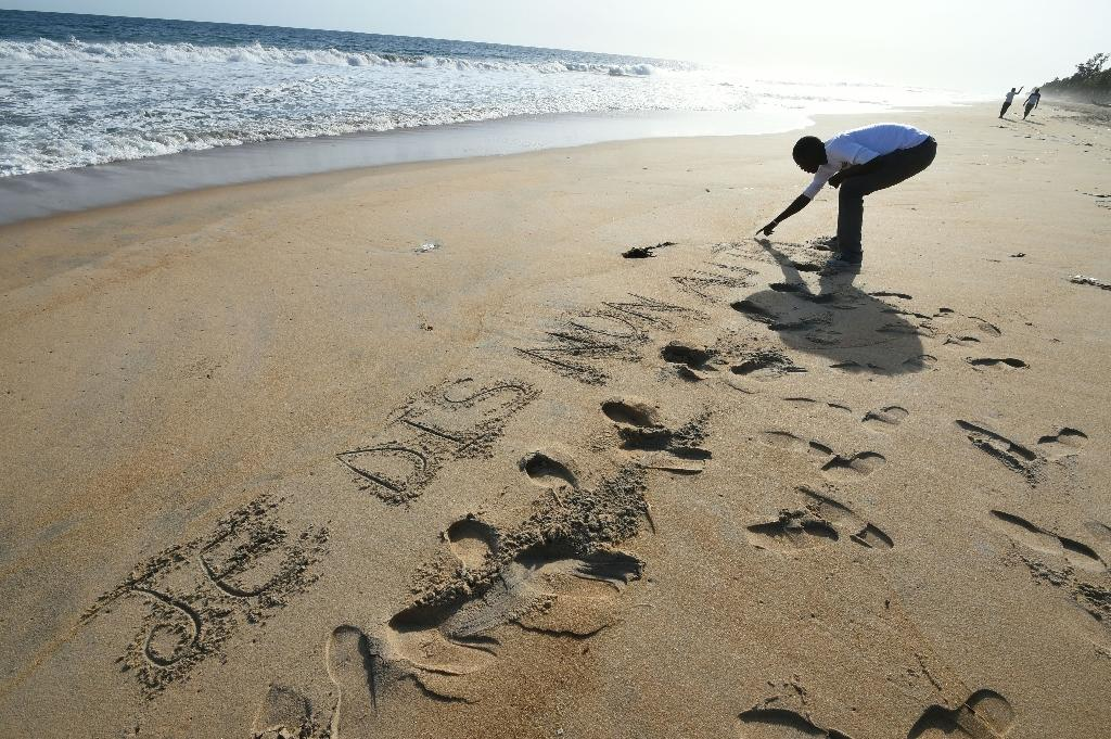 "A man scratches in the sand the words, ""I say no to terrorism,"" close to the Hotel Etoile du Sud, in Grand-Bassam, Ivory Coast on March 16, 2016 (AFP Photo/Sia Kambou)"