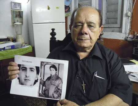 Raul Borges holds a picture of his son in his house in Havana