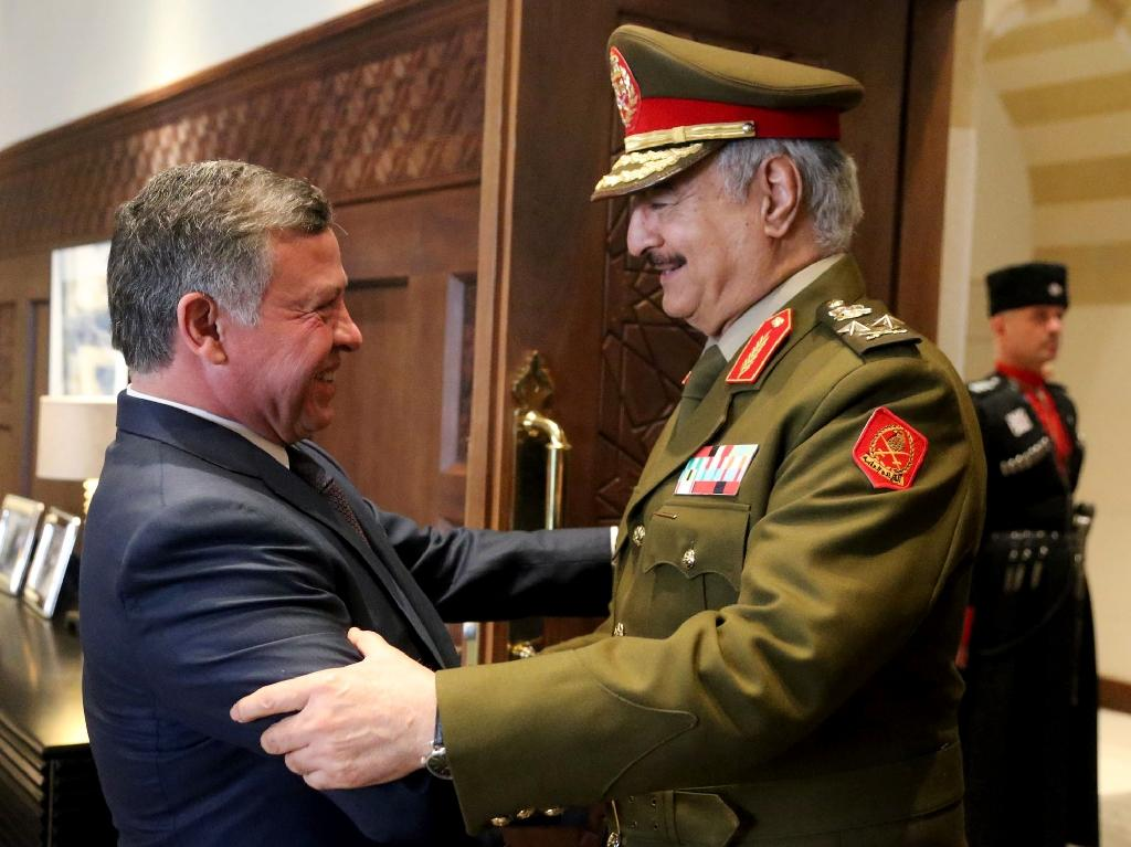Jordan's King Abdullah II (left) shakes hands with Libyan army chief General Khalifa Haftar at the Royal Palace in Amman, on April 13, 2015