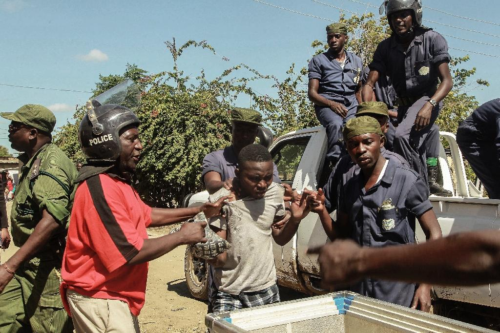 Zambian police apprehend an alleged looter in the Zingalume Compound on April 19, 2016 (AFP Photo/Salim Dawood)