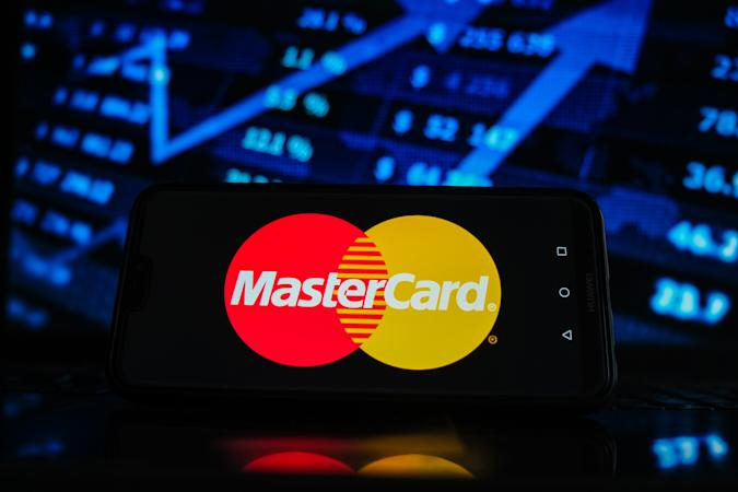 POLAND - 2021/02/05: In this photo illustration a Mastercard logo seen displayed on a smartphone screen with stock market graphic on the background. (Photo Illustration by Omar Marques/SOPA Images/LightRocket via Getty Images)